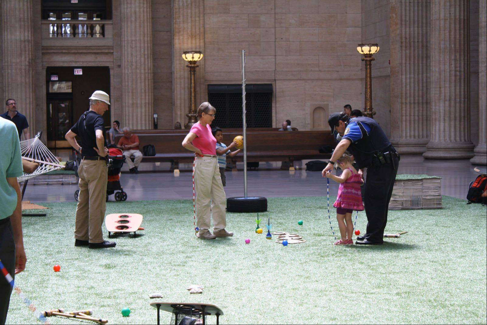 People play backyard games in the Great Hall of Union Station, part of a winning design created by Buffalo Grove native Corey Nissenberg's team for a Chicago competition.