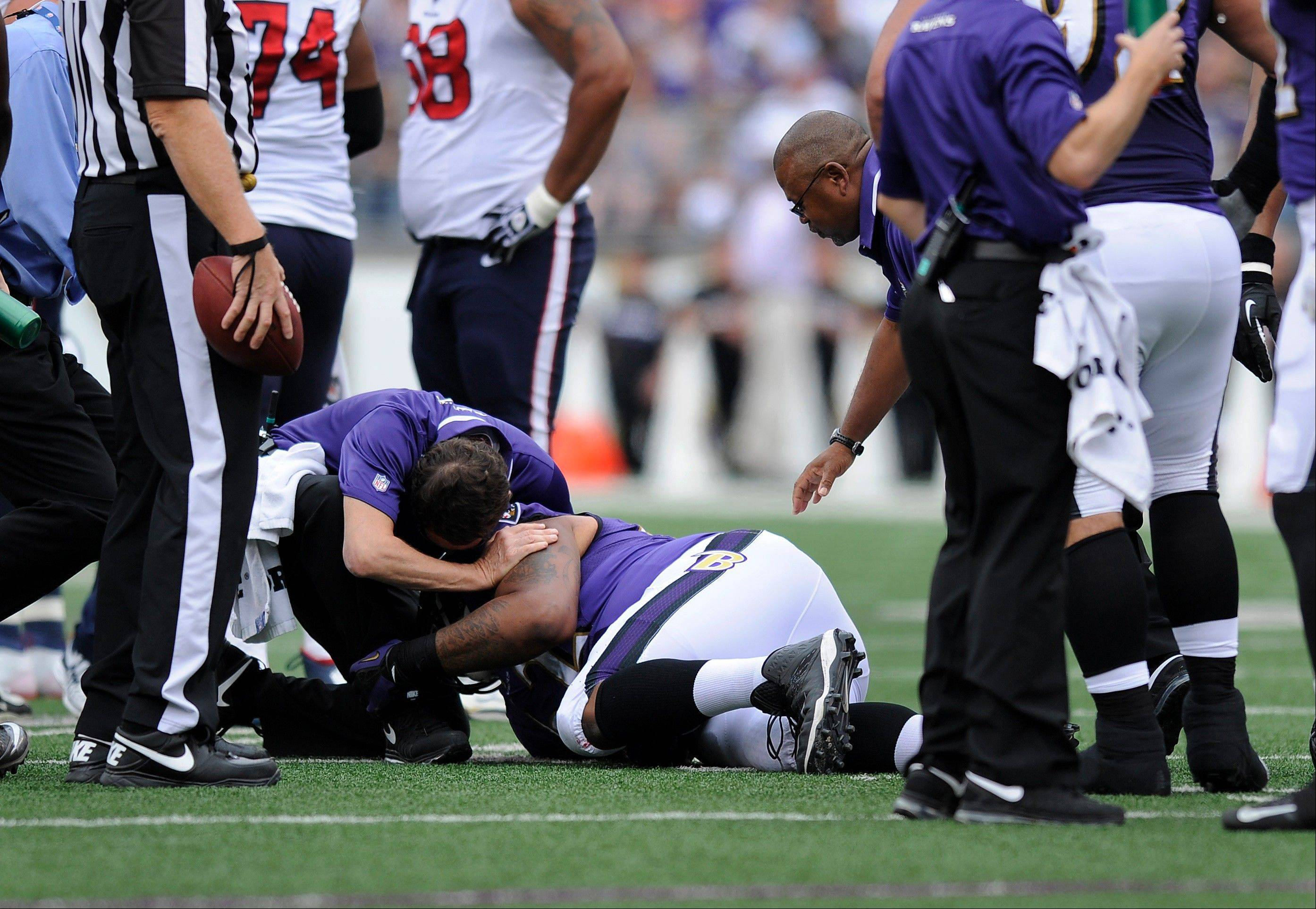 Baltimore Ravens nose tackle Terrence Cody is attended to by Ravens staff after he injured himself on a play in the first half of an NFL football game against the Houston Texans, Sunday, Sept. 22, 2013, in Baltimore.
