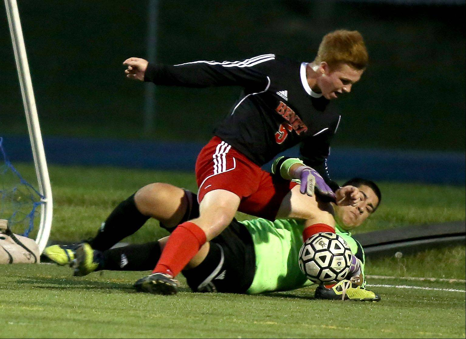 Benet Academy's Paddy Lawler collides with West Chicago goalkeeper Paolino Mansera as he makes a save in boys soccer action on Monday.