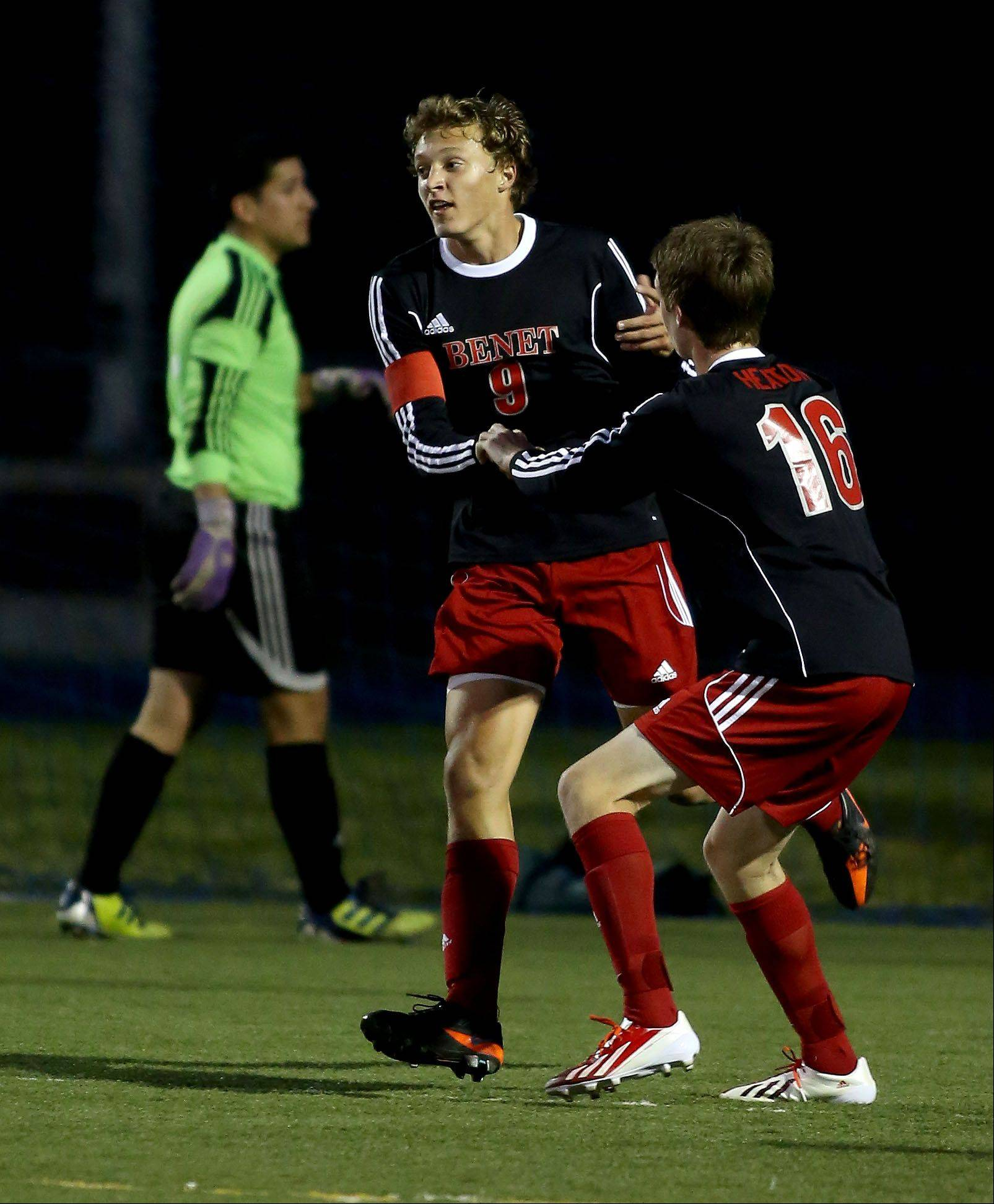 Michael Rindler of Benet Academy, left, is congratulated by teammate Andrew Heaton, after he made a second goal in the first half against West Chicago in boys soccer action on Monday.