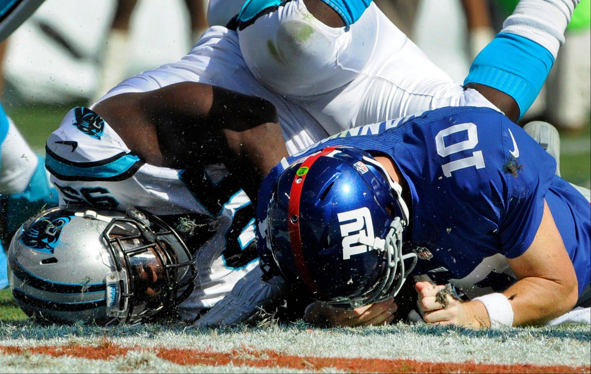 New York Giants' Eli Manning (10) is sacked by Carolina Panthers' Charles Johnson (95) during the second half of a game Sunday in Charlotte, N.C.. There have been 97 sacks in Week 3, five short of the record set in 1986's 11th week.