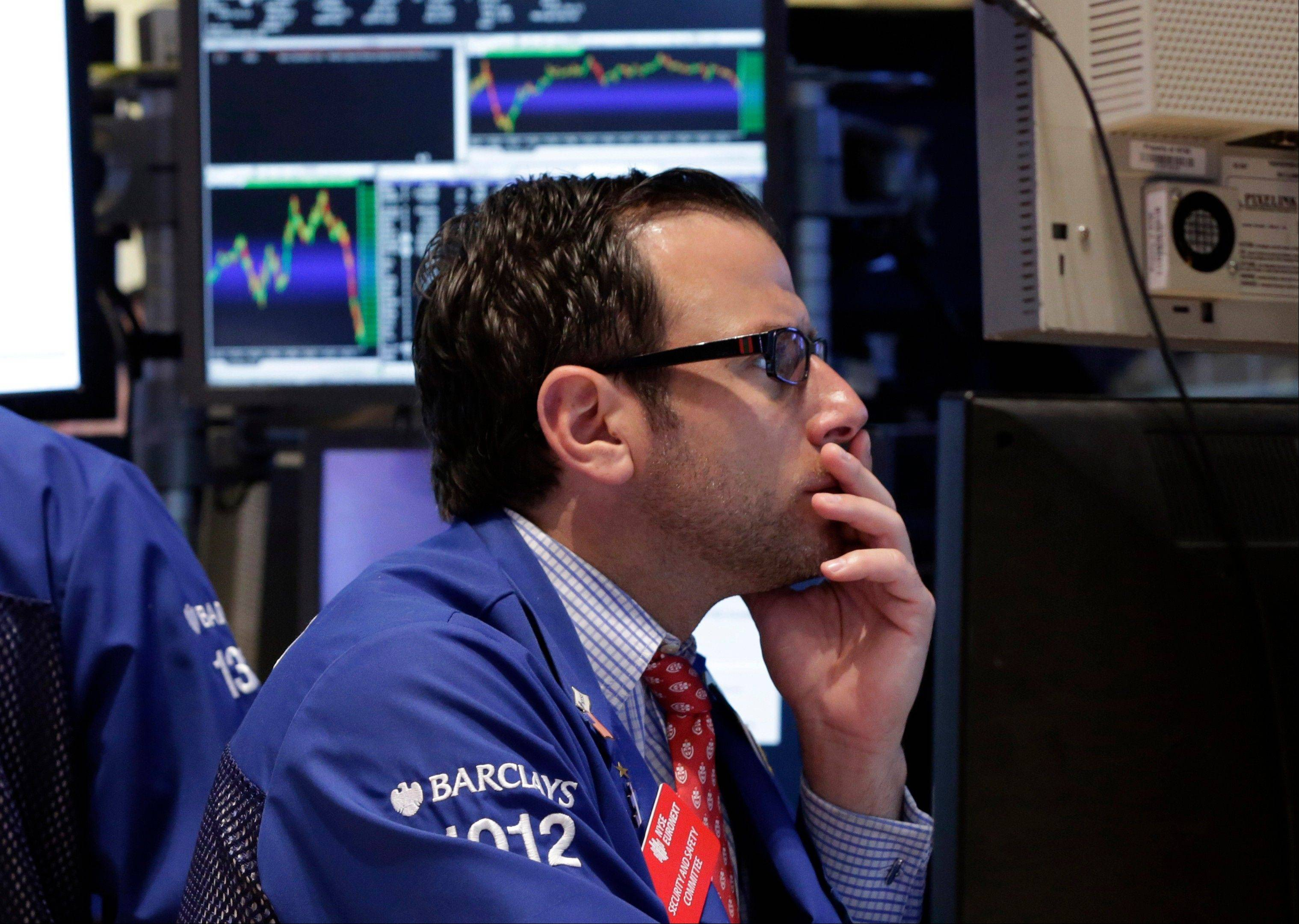 Specialist Michel Pistillo works Monday at his post on the floor of the New York Stock Exchange. U.S. stock futures are mixed with a confrontation over the budget looming.