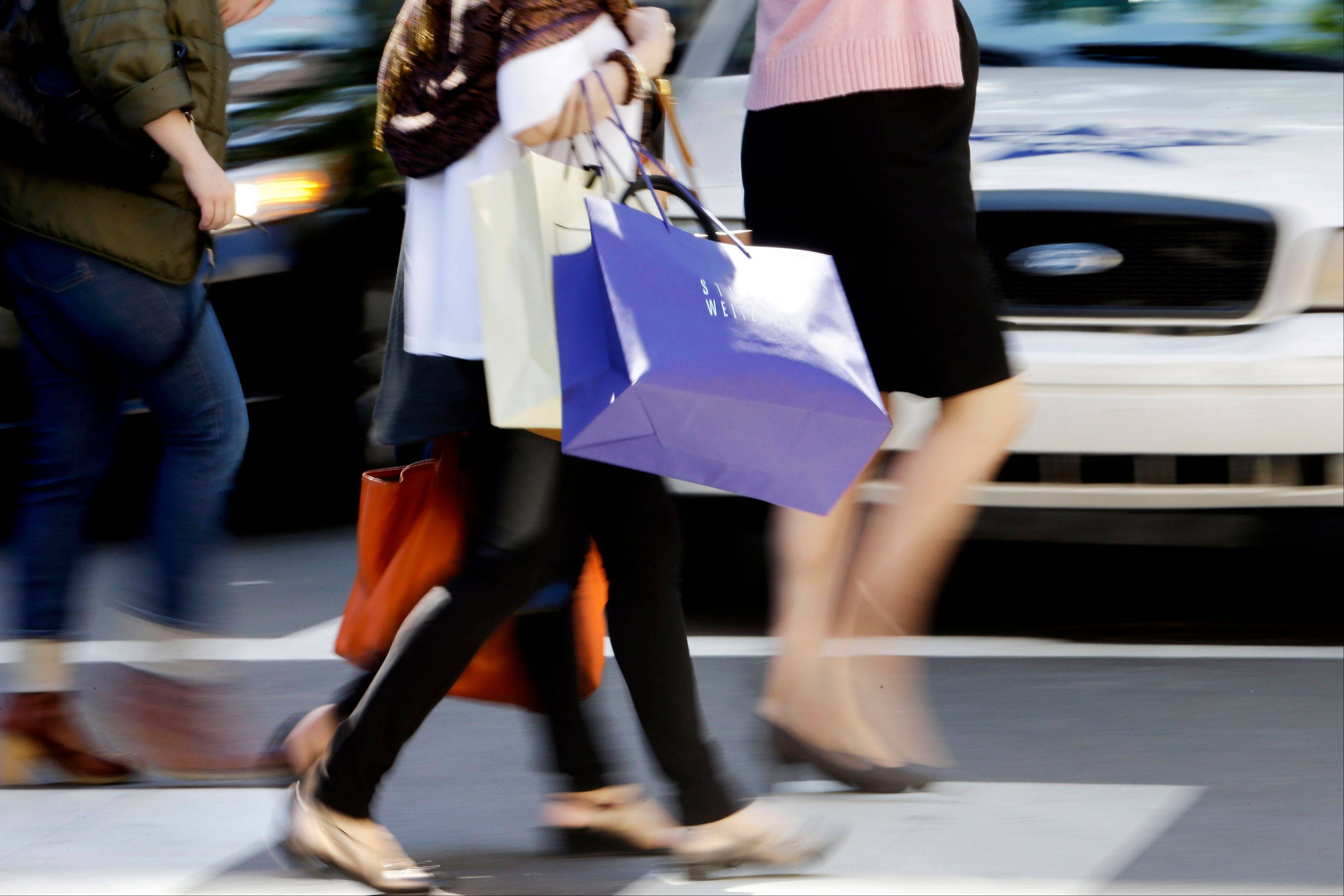 Pedestrians with shopping bags cross a street in Philadelphia. Americans' confidence in the economy fell slightly in September from August, as many became less optimistic about hiring and pay increases over the next six months.