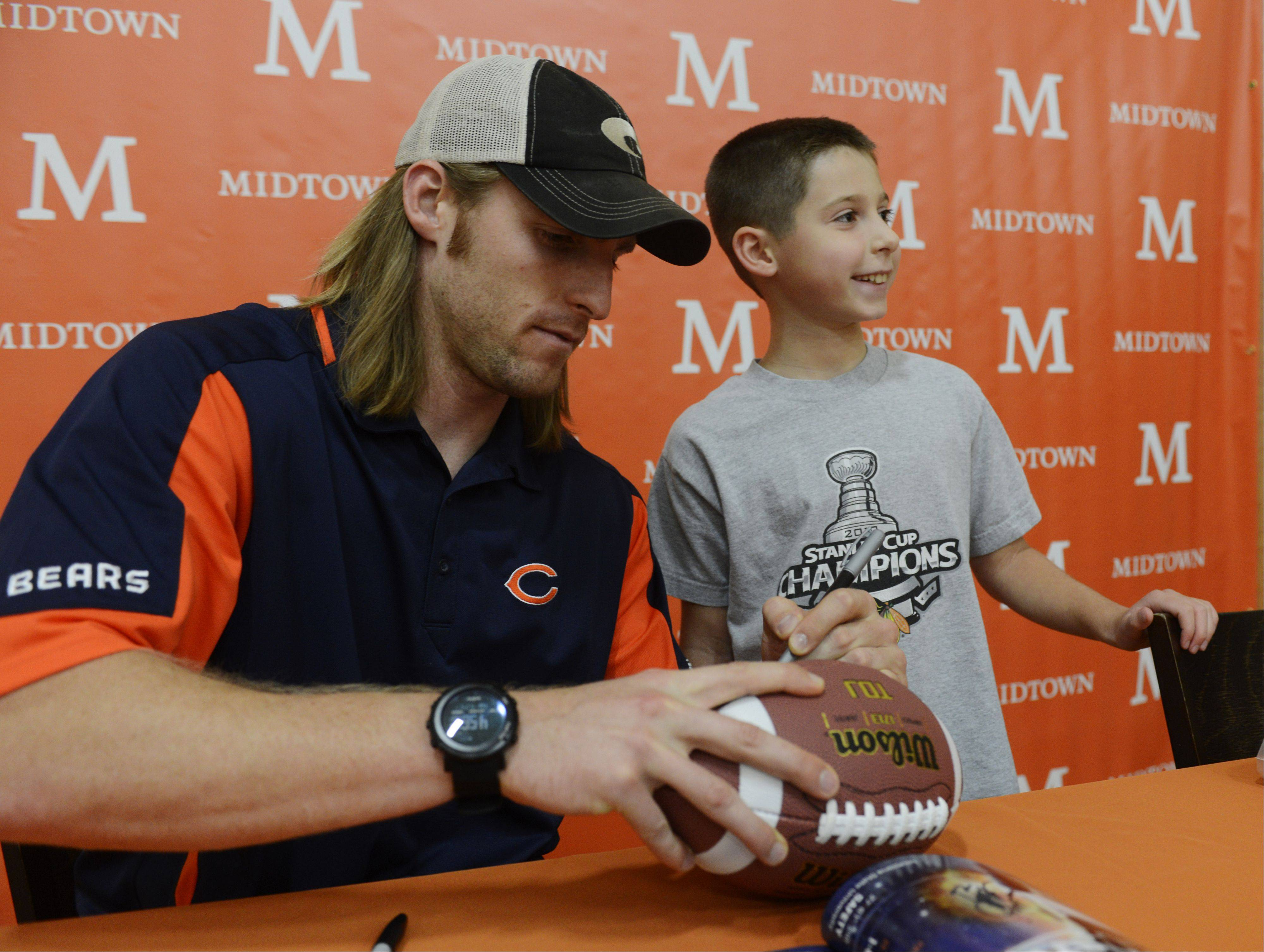 JOE LEWNARD/jlewnard@dailyherald.com Chicago Bears safety Craig Steltz signs a football for Connor Nichols, 9, of Palatine during a fitness event Tuesday for children at the Midtown Athletic Club in Palatine Tuesday. The event served as a kickoff to Saturday�s Midtown 5K Run & Walk to benefit Bears Care.
