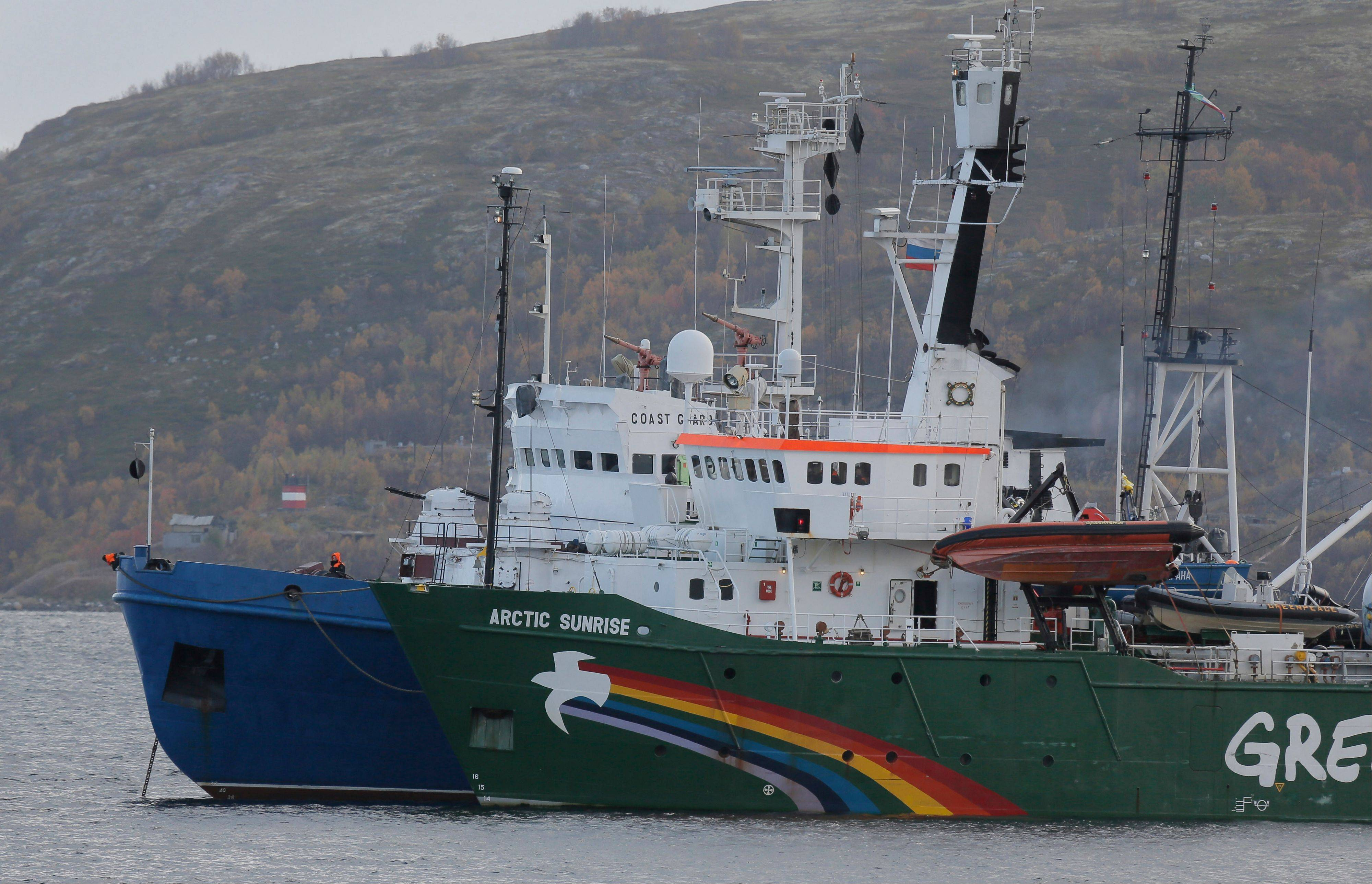 Greenpeace ship 'Arctic Sunrise' is escorted by a Russian coast guard boat, in Kola Bay at the military base Severomorsk on the Kola Peninsula in Russia, at dawn Tuesday, Sept. 24, 2013. Russia has filed piracy charges against Greenpeace activists who tried to board an offshore drilling platform in the Arctic owned by state-controlled natural gas company Gazprom.