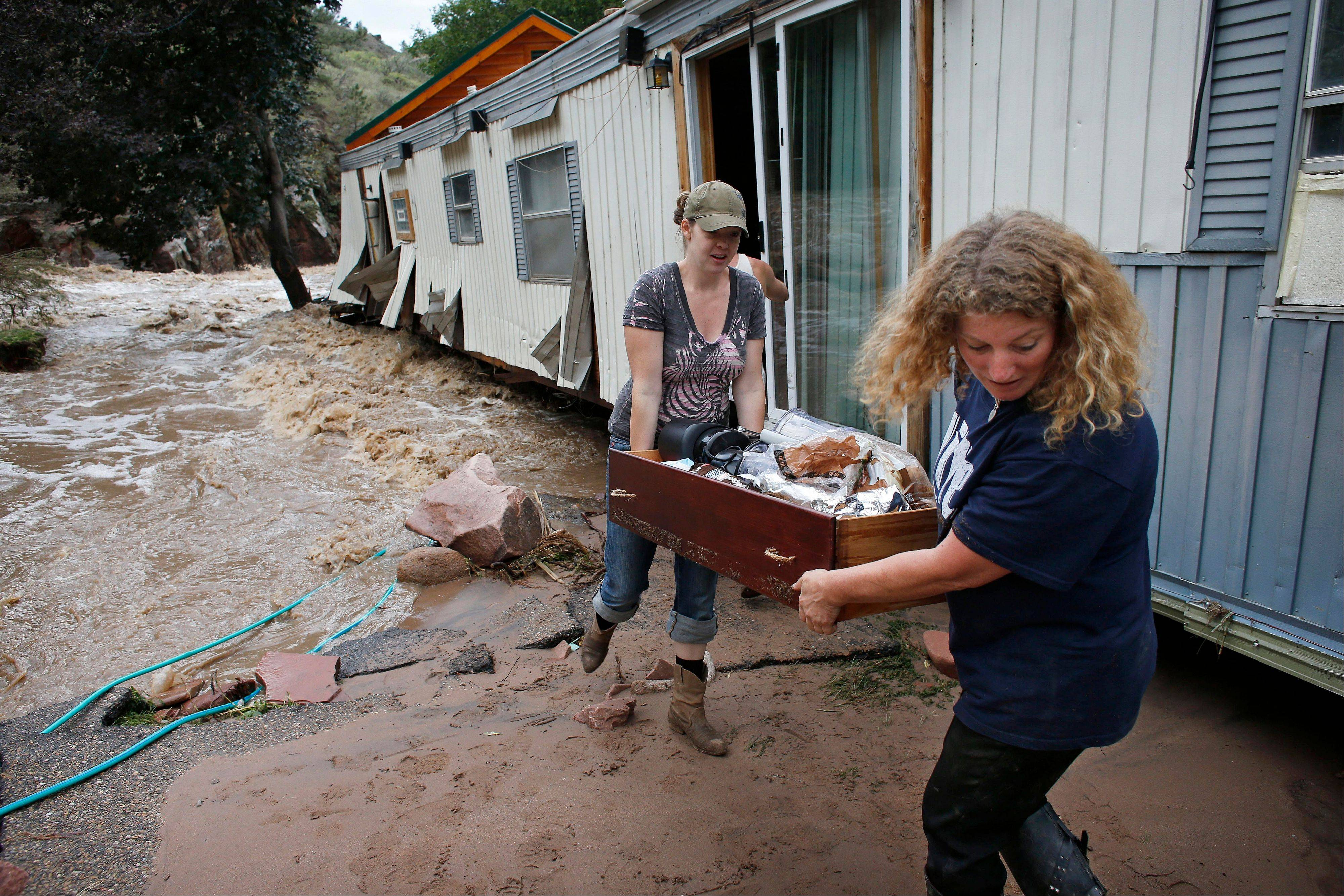 "Holly Robb, left, and her neighbor Pam Bowers salvage belongings after storms that raged through the Rocky Mountain foothills in Lyons, Colo. Two low-lying trailer parks in the small town, 20 minutes to the north of Boulder, bore the brunt of the recent flooding. ""I don't think we'll ever be able to go back,"" said Robb."