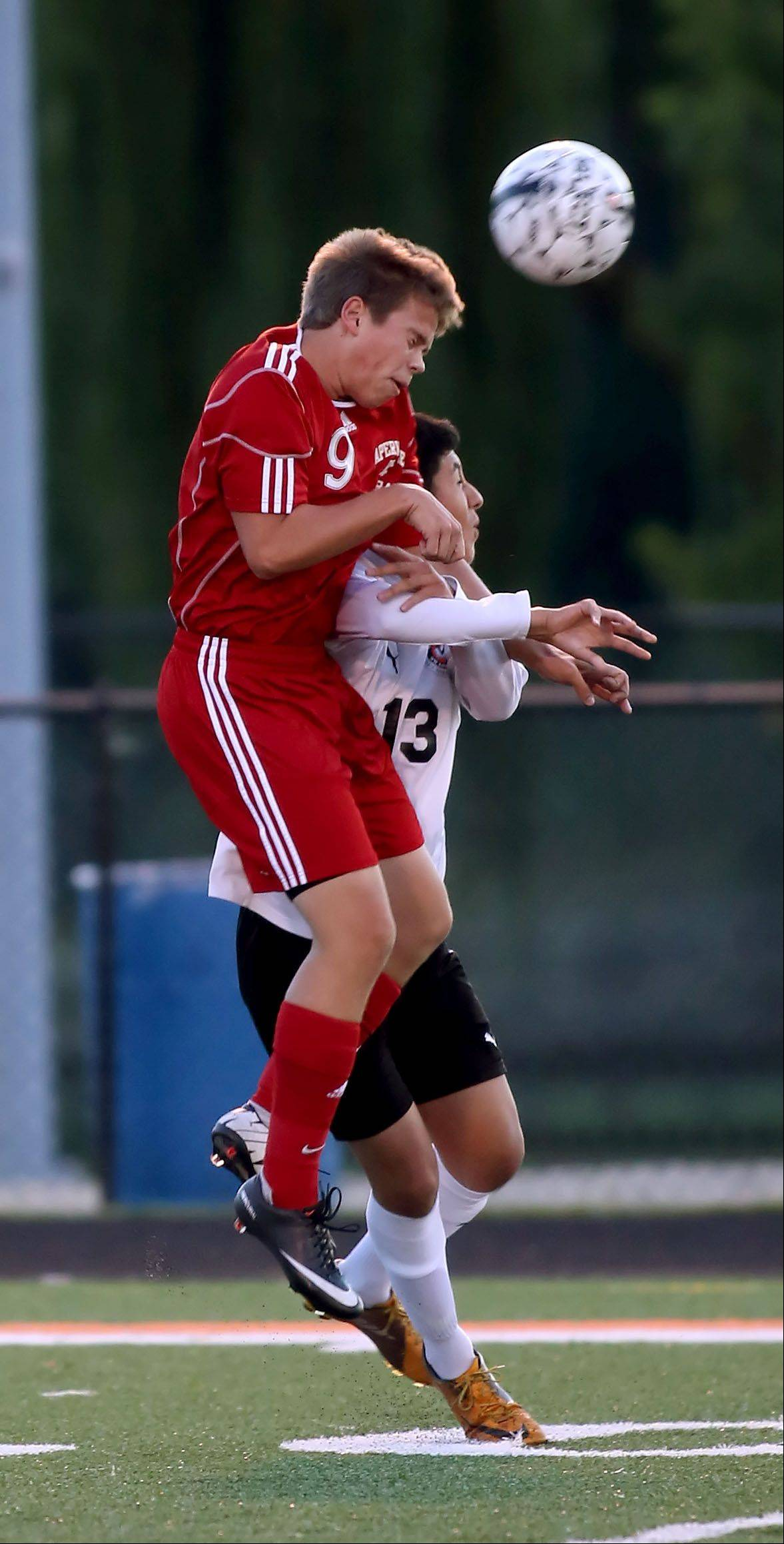 Jordi Heeneman of Naperville Central, left, and Jose Perez, right, of Wheaton Warrenville South, go up for the header during boys soccer action on Tuesday in Wheaton.