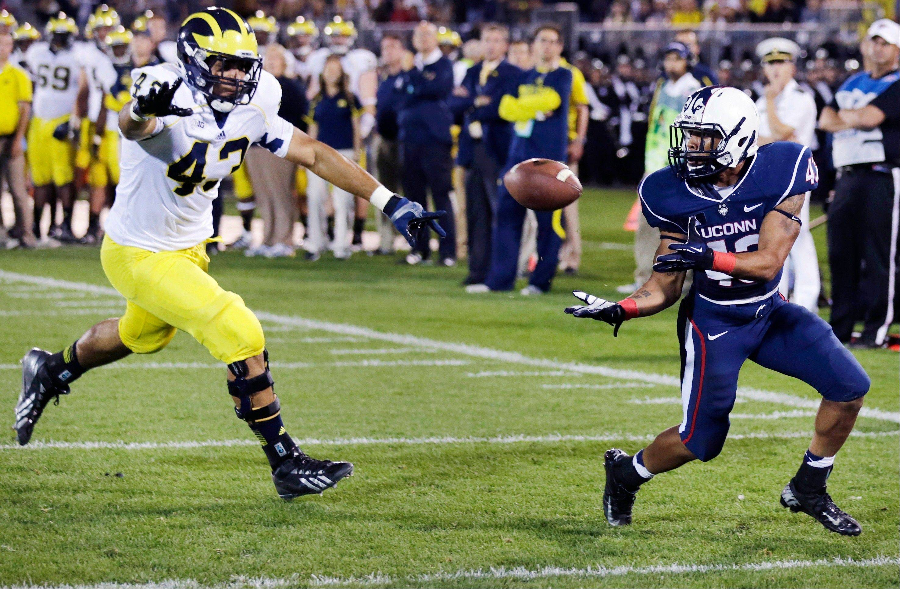 Connecticut running back Lyle McCombs, right, hauls in a touchdown pass against Michigan defensive lineman Chris Wormley during the second quarter of last Saturday�s game in East Hartford, Conn. The Wolverines came back from a 14-point, second-half deficit to win 24-21.