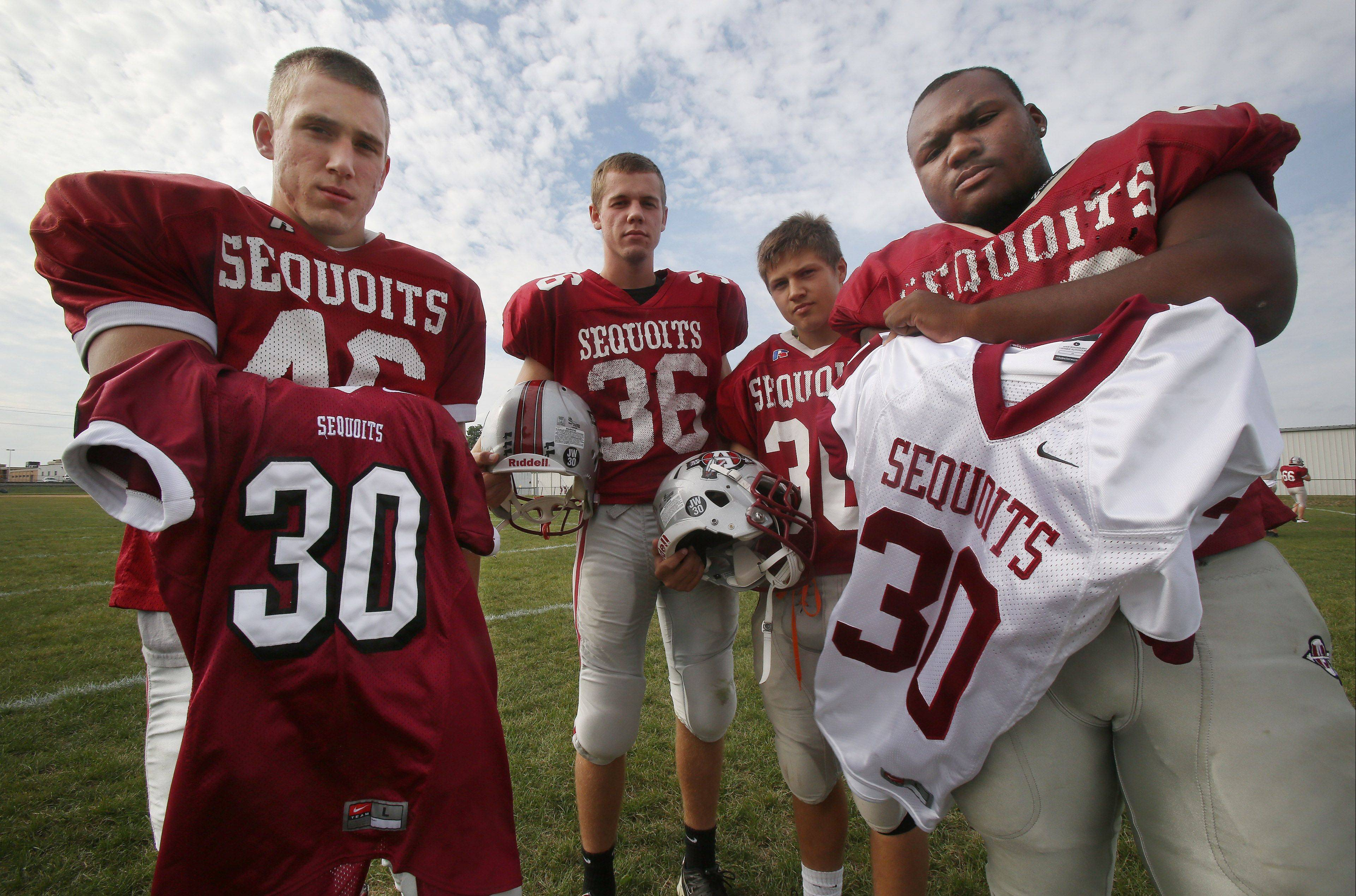 Antioch football players Robert Ritacca, left, Christian Norris, Wesley Zegan and Malik Jackson hold versions of jersey No. 30 in honor of former teammate Joel Wittkamp, who died in a car accident in February. Every week this season, a different Antioch senior wears No. 30 in memory of Wittkamp.