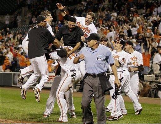Members of the Baltimore Orioles mob teammate Nolan Reimold (14) after he scored the winning run against the Red Sox on Sept. 28, 2011, at home. Baltimore won 4-3, and Boston was eliminated from the playoffs after Tampa Bay beat the Yankees in extra innings minutes after Boston�s loss.