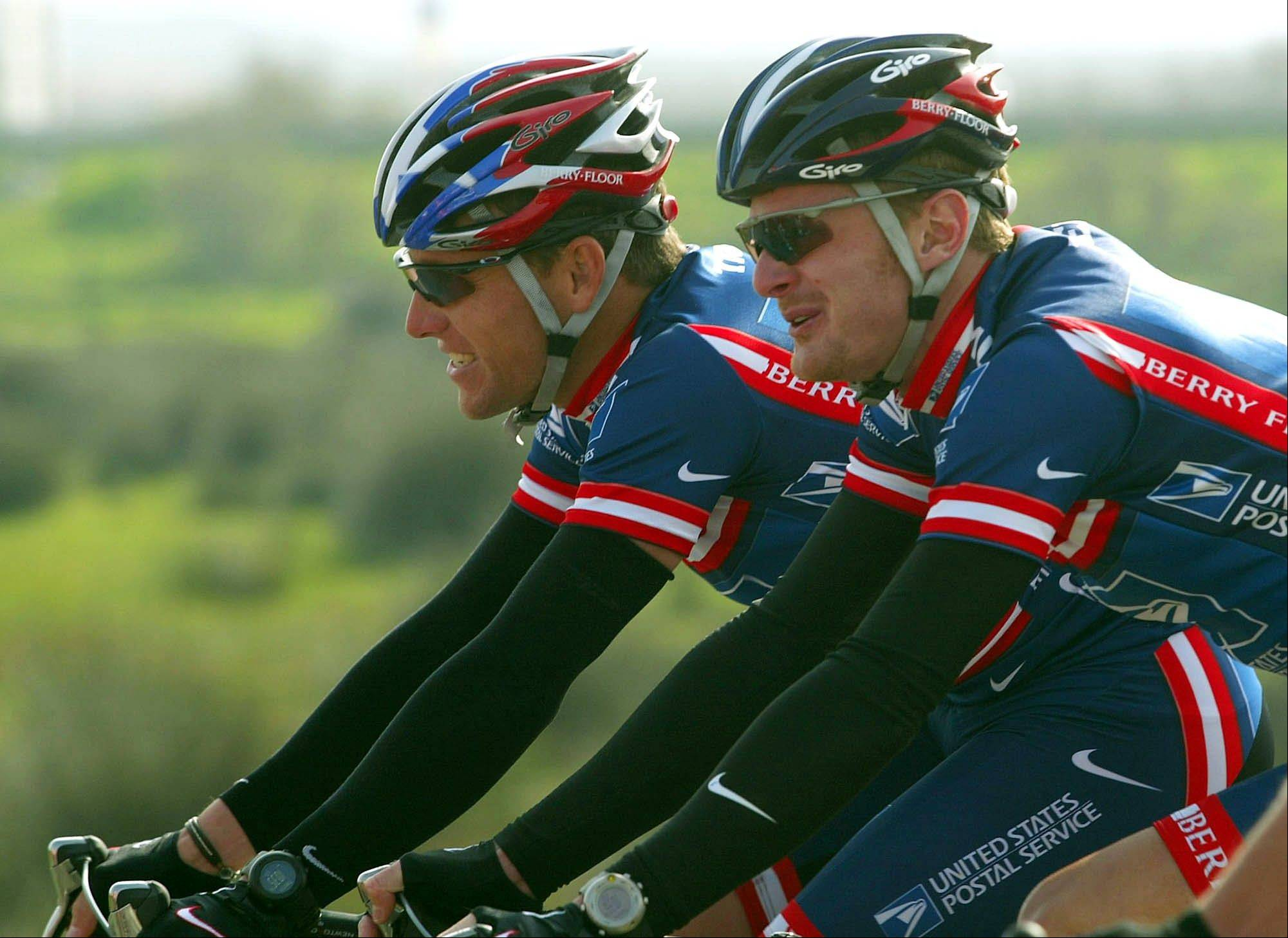 Lance Armstrong, left, and Floyd Landis, then both members of the U.S. Postal Service cycling team, ride side by side during a 2004 race in Portugal. Attorneys for the federal government and Landis urged a judge not to dismiss the whistle-blower lawsuit against Armstrong, arguing the Texan and former team officials should have to pay back at least $40 million they were paid in a sponsorship deal with the U.S. Postal Service.
