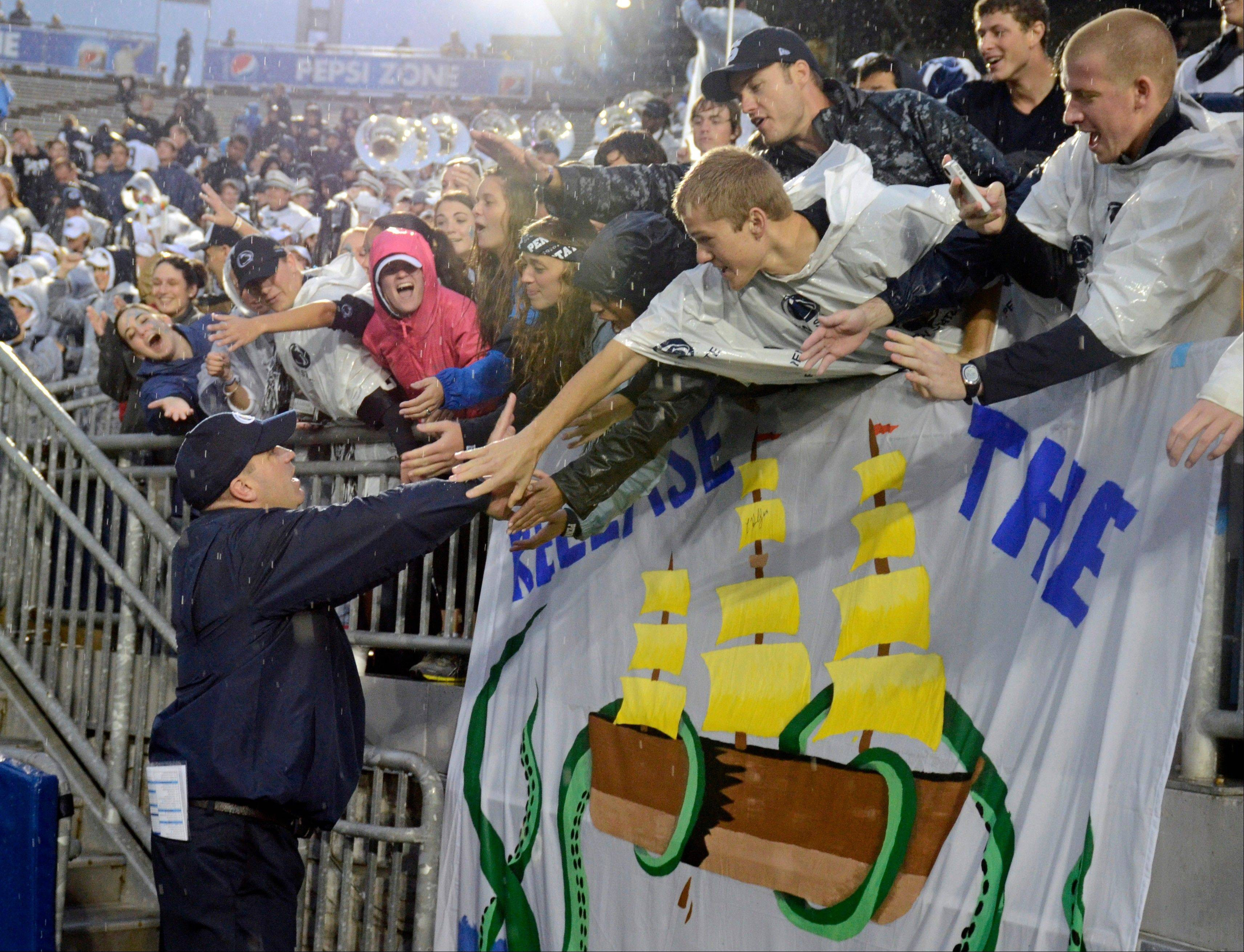 Penn State head coach Bill O' Brien, left, thanks fans in the student section of Beaver Stadium after defeating Kent State 34-0 on Saturday in State College, Pa.