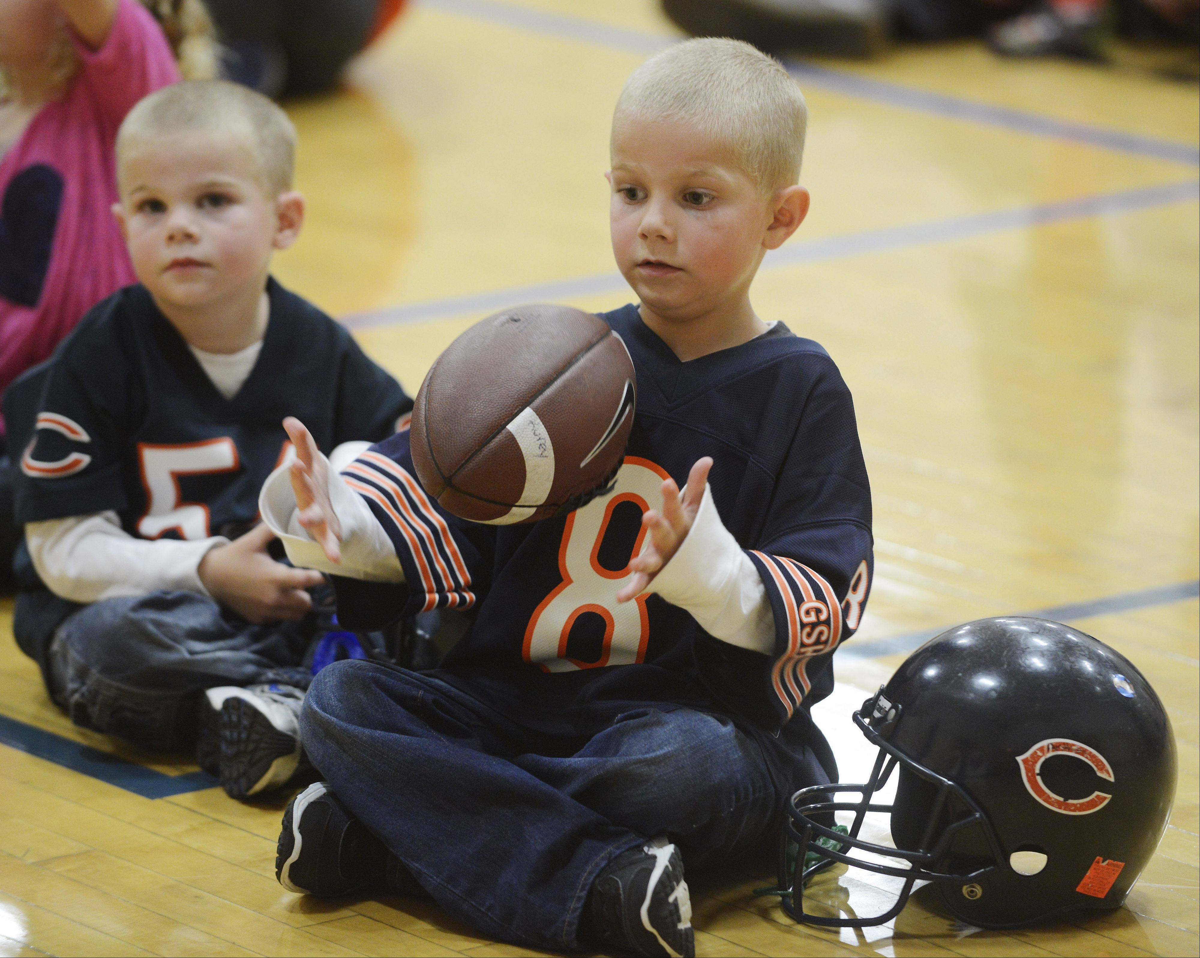 JOE LEWNARD/jlewnard@dailyherald.comAnthony Kurey, 4, of Palatine flips his football Tuesday in his hands while attending a fitness event with his brother, Joey, 3, at the Midtown Athletic Club in Palatine. Joining them was Chicago Bears safety Craig Steltz.