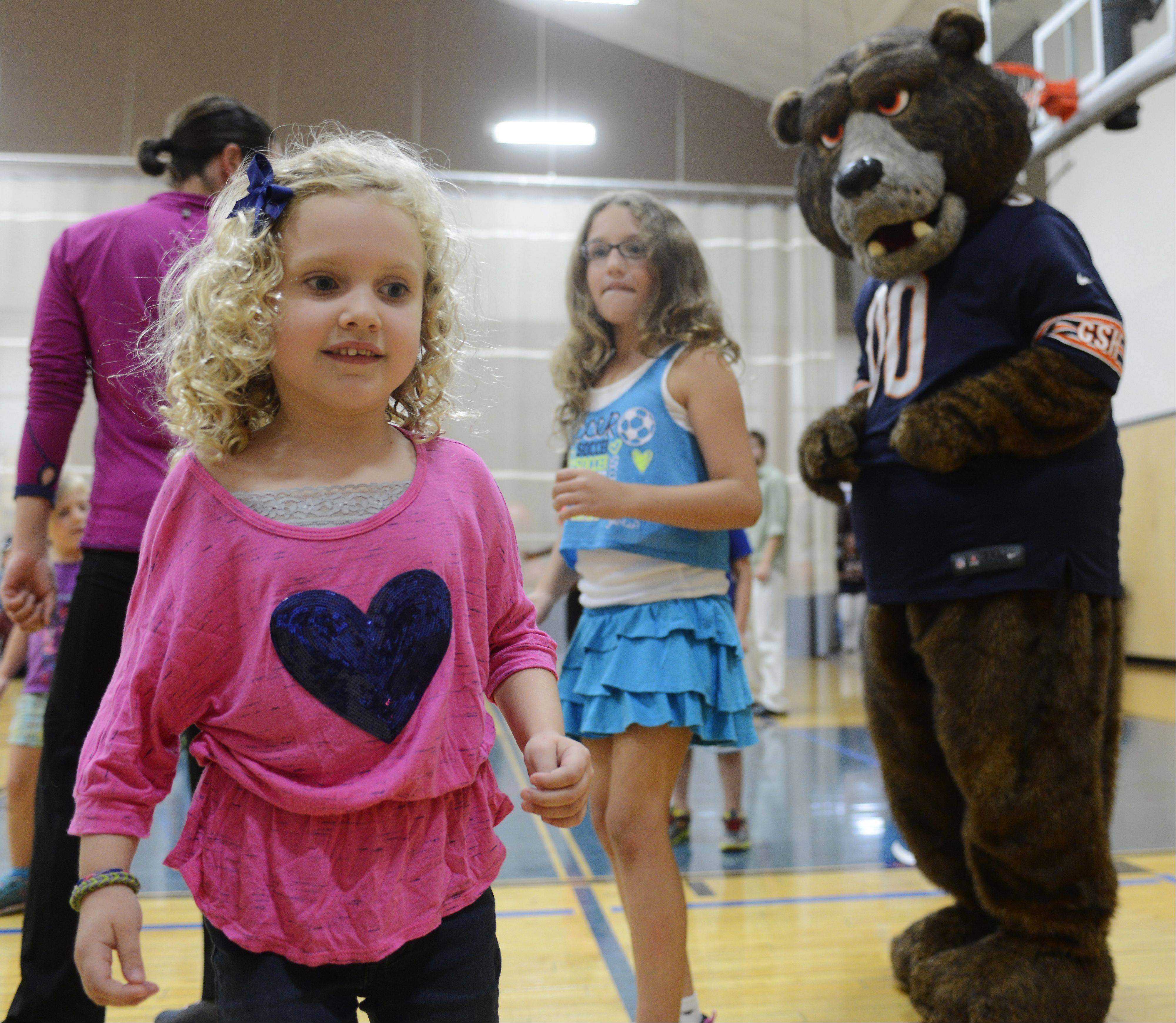 JOE LEWNARD/jlewnard@dailyherald.comSamantha Fetzer, 5, of Arlington Heights, dances with Staley 'Da Bear' during a fitness event Tuesday for children at the Midtown Athletic Club in Palatine. Joining them was Chicago Bears safety Craig Steltz.