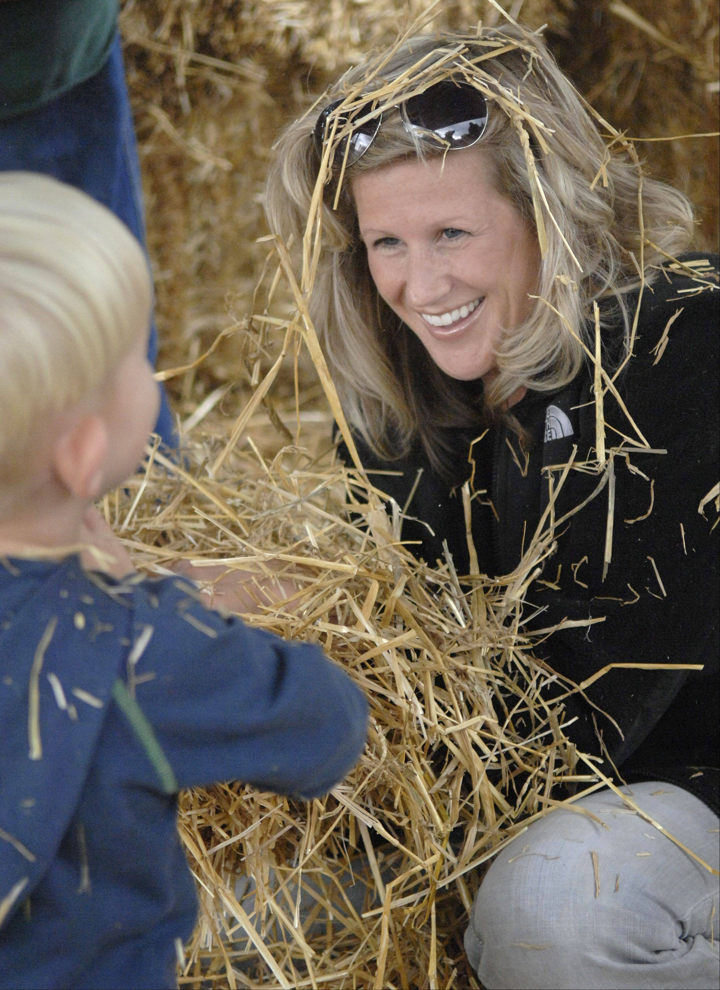 Heather Schroeder and son, Matthew, 2, of Huntley have a straw fight while their scarecrow's finishing touches are put on by Matthew's dad, Brad, at a previous Huntley Fall Fest. The family assembled their own scarecrow at the festival. This year's festival begins Friday and runs through Sunday.