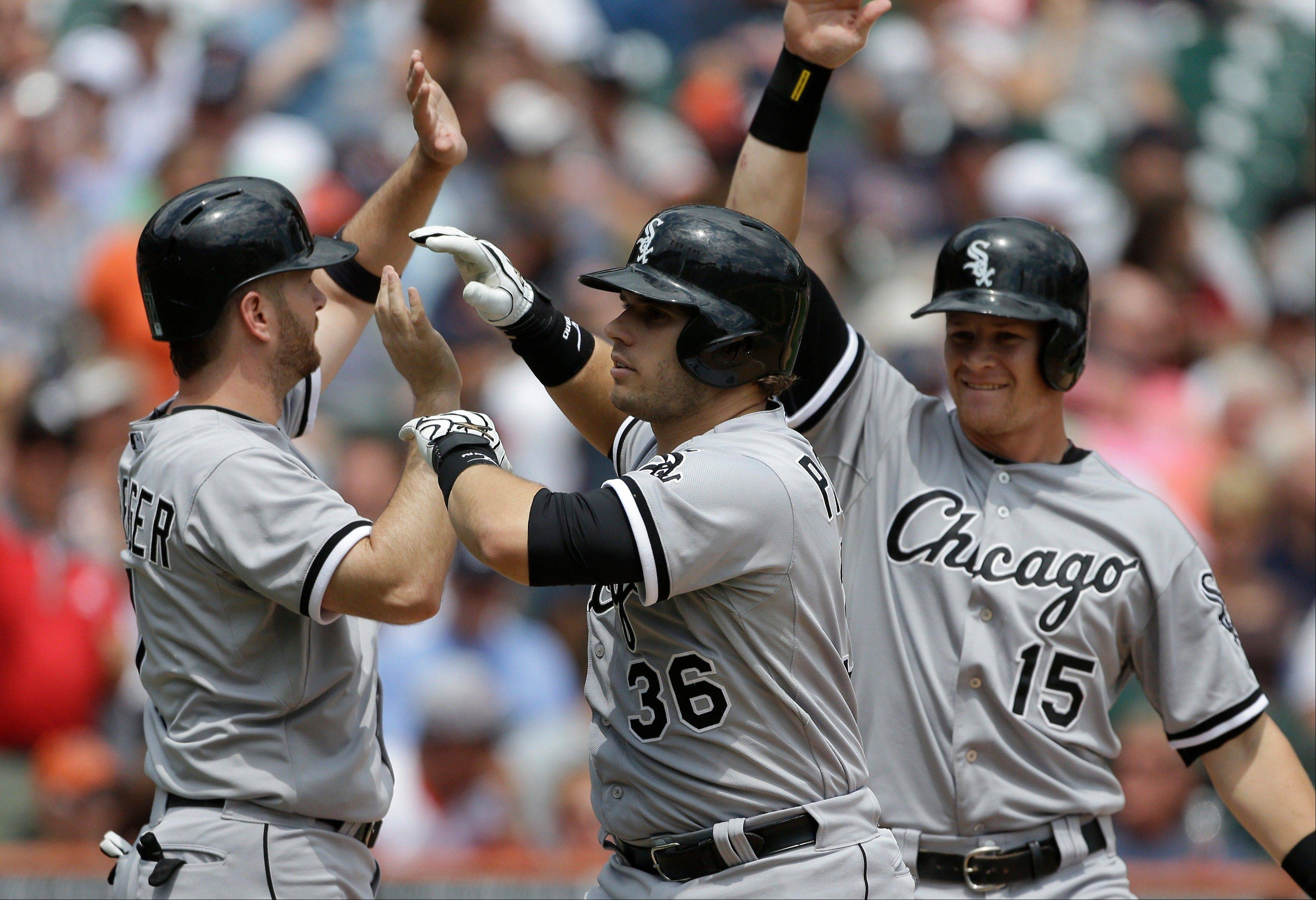 Josh Phegley, (36) is congratulated by teammates Jeff Keppinger, left, and Gordon Beckham (15) after his grand slam during the sixth inning of a baseball game against the Detroit Tigers in Detroit, Thursday, July 11, 2013.