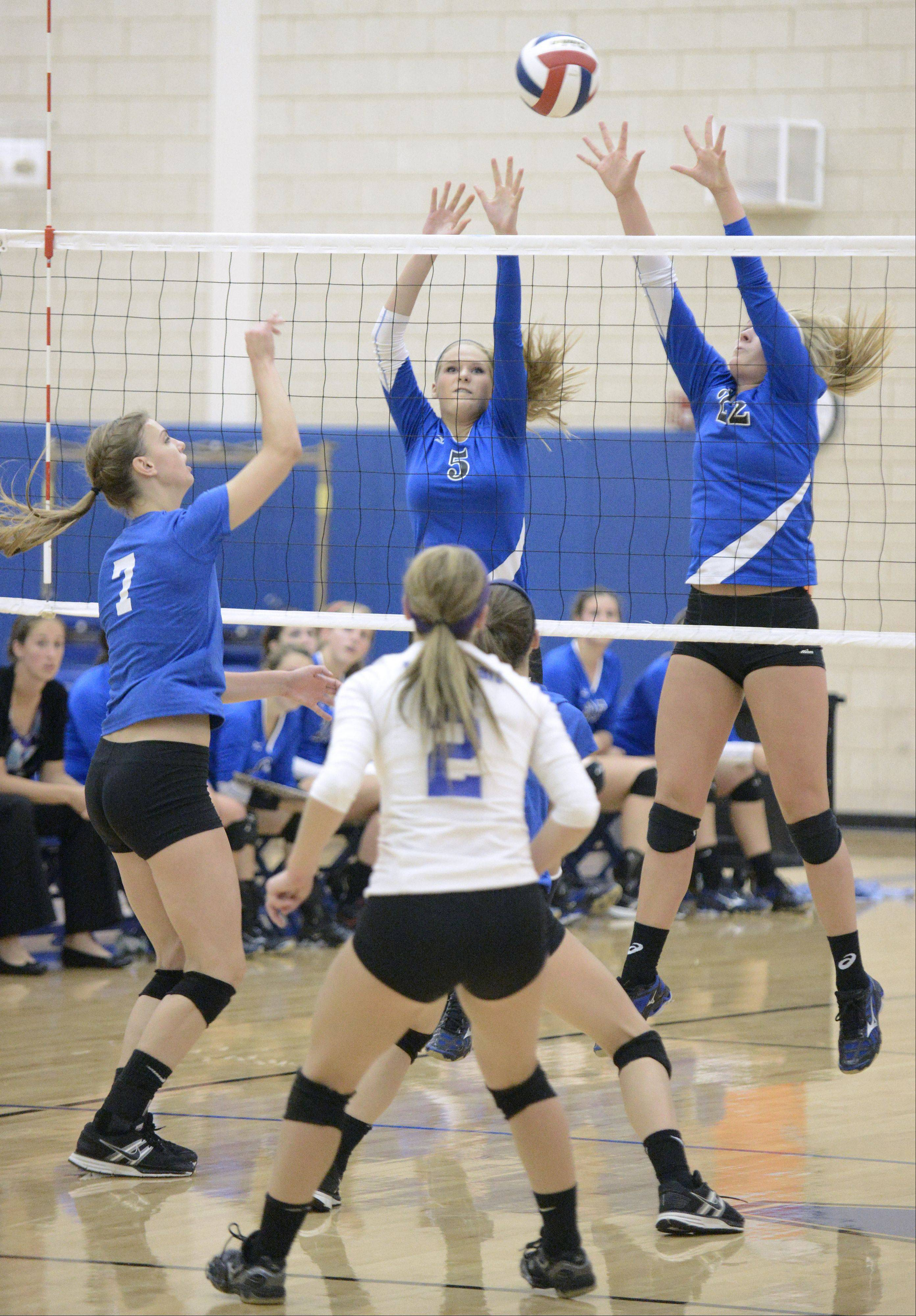 Geneva's Kyley Thompson and Maddie Courter deflect a spike by St. Charles North's Taylor Krage in the first match on Tuesday, September 24.