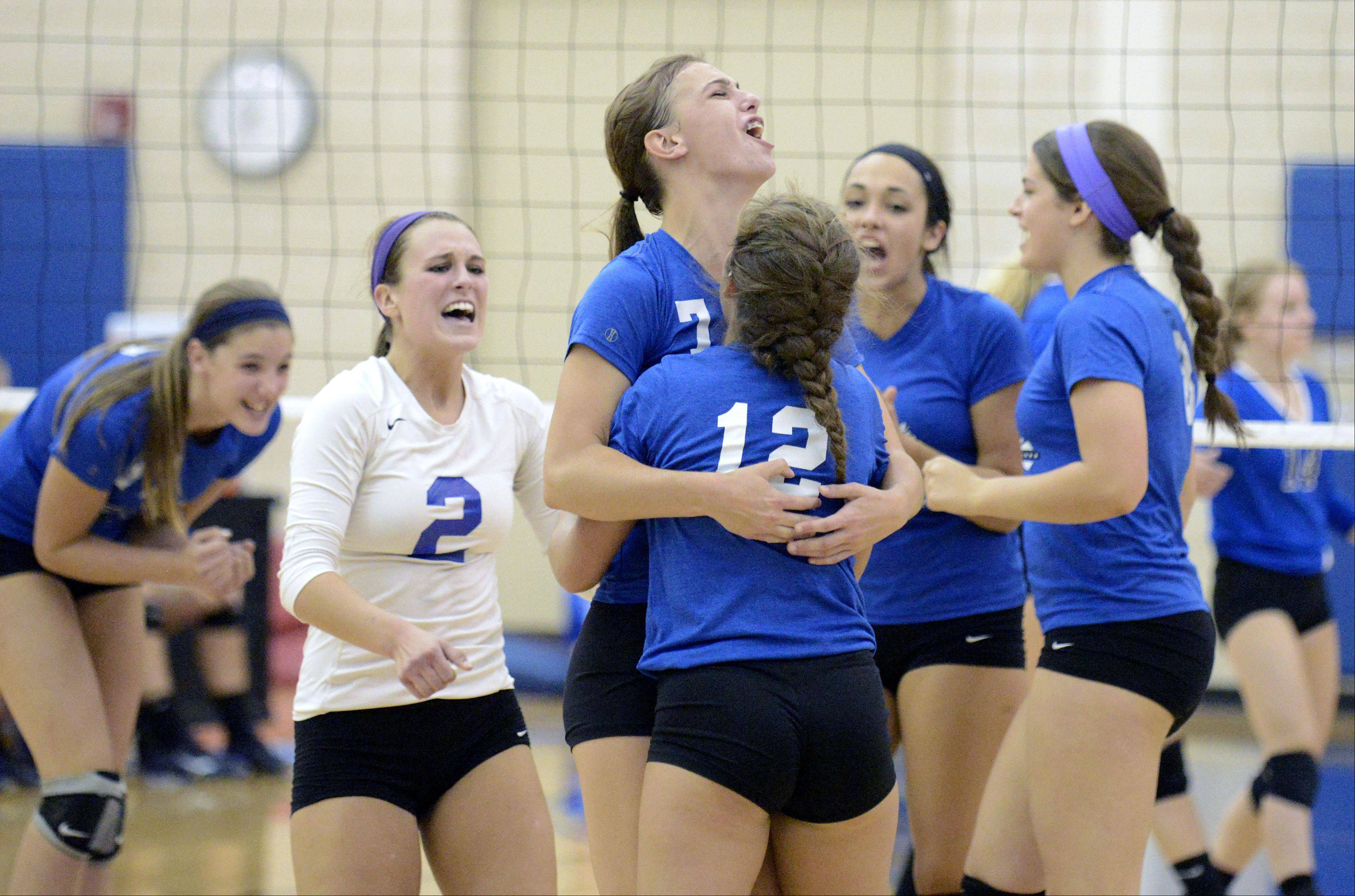 St. Charles North's Taylor Krage (7) hugs teammate Sydney Wohlert after scoring a point over Geneva in the first match on Tuesday, September 24.