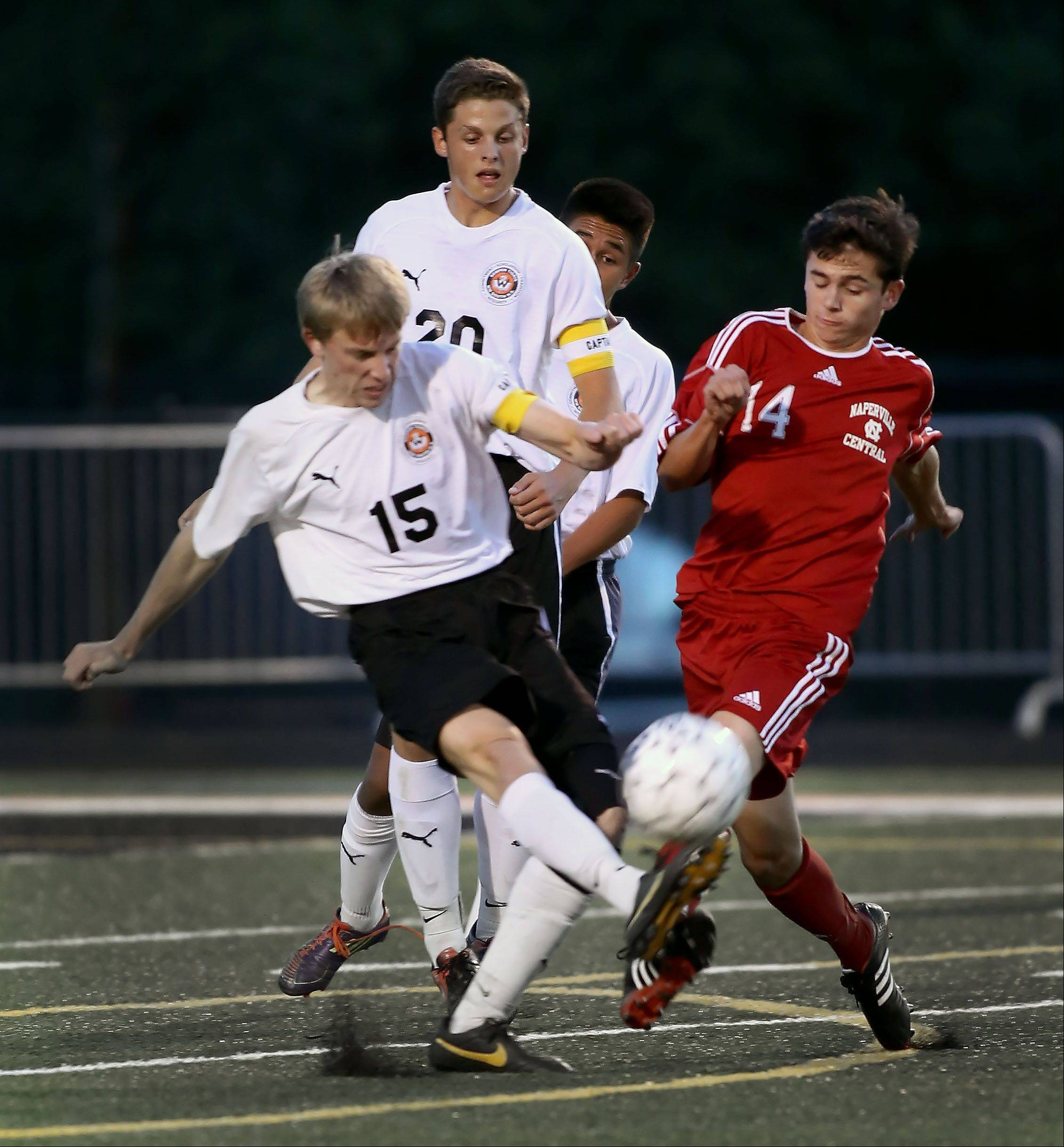 Joe Spera, left, of Wheaton Warrenville South and David Murphy, right, of Naperville Central battle for the ball during boys soccer on Tuesday in Wheaton.