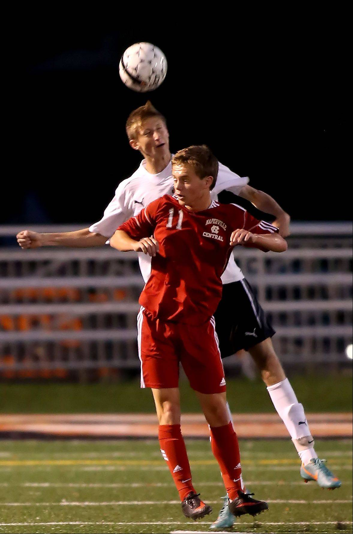 Ian Daniel of Wheaton Warrenville South, behind, heads the ball from Ben Border of Naperville Central during boys soccer action on Tuesday in Wheaton.