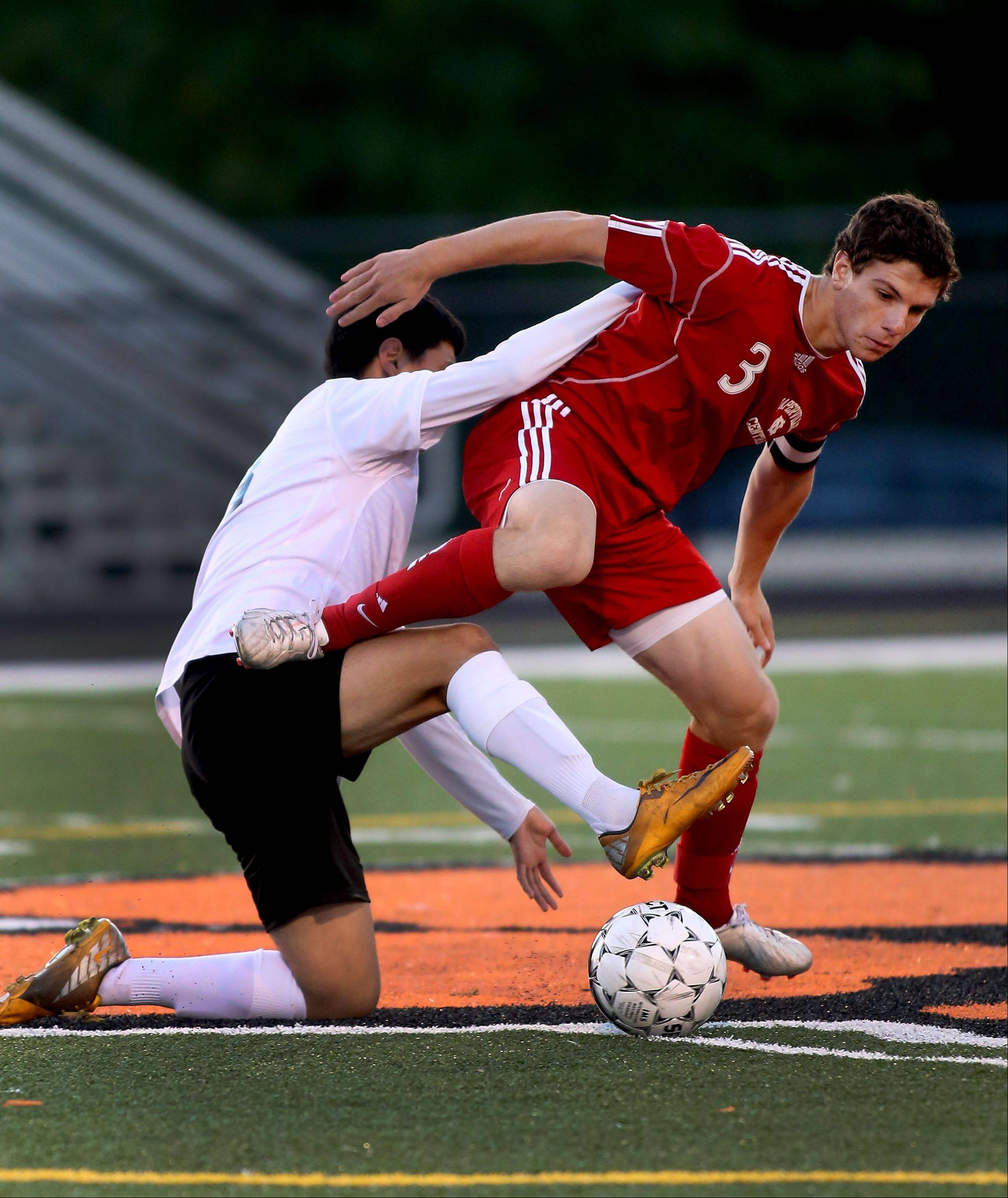 Jay Tegge of Naperville Central gets tangled up with Jose Perez, left, of Wheaton Warrenville South during boys soccer action on Tuesday in Wheaton.