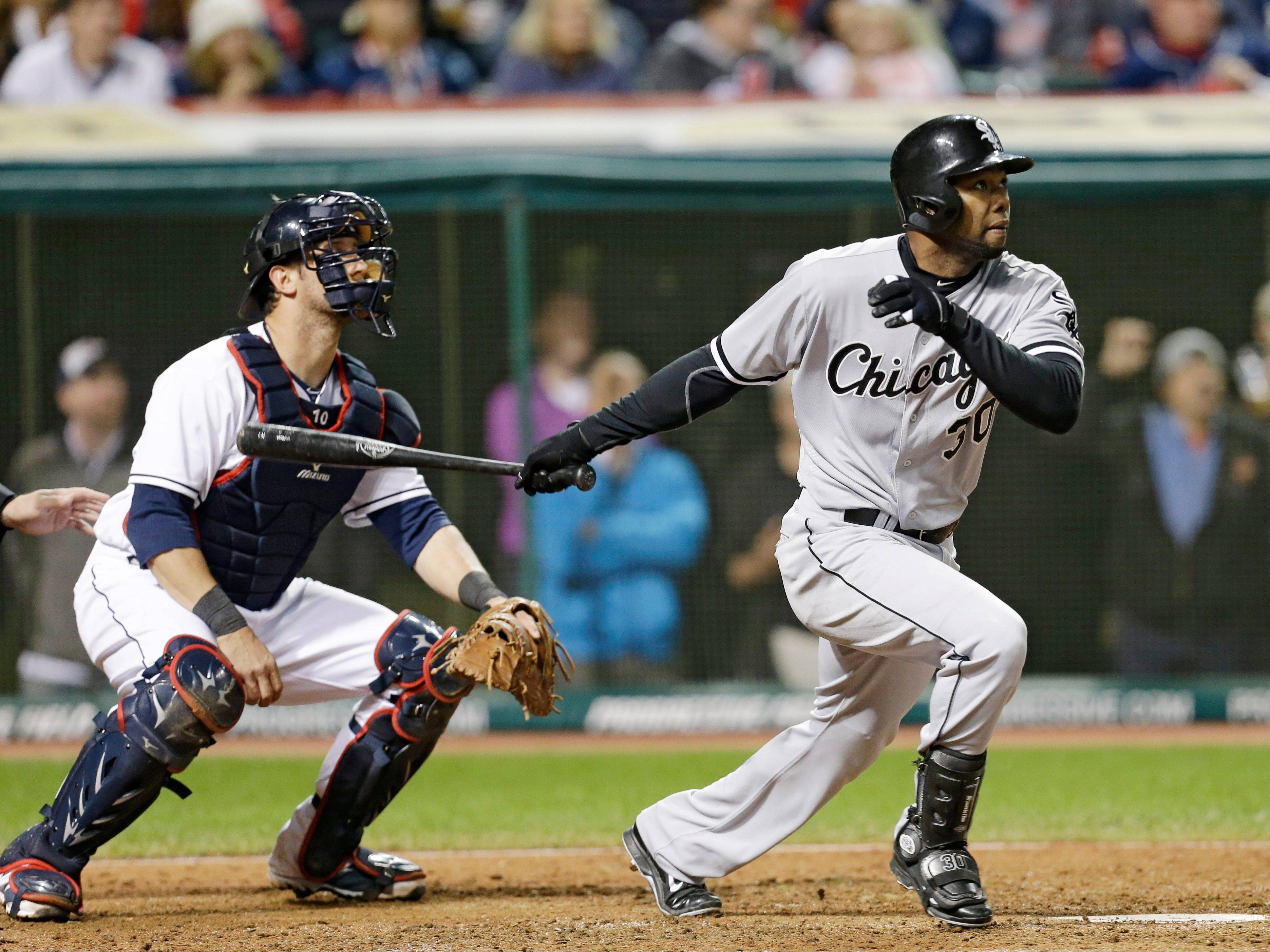 The Chicago White Sox's Alejandro De Aza hits a solo home run off Cleveland Indians relief pitcher Chris Perez in the ninth inning of a baseball game, Tuesday, Sept. 24, 2013, in Cleveland. Indians catcher Yan Gomes watches.