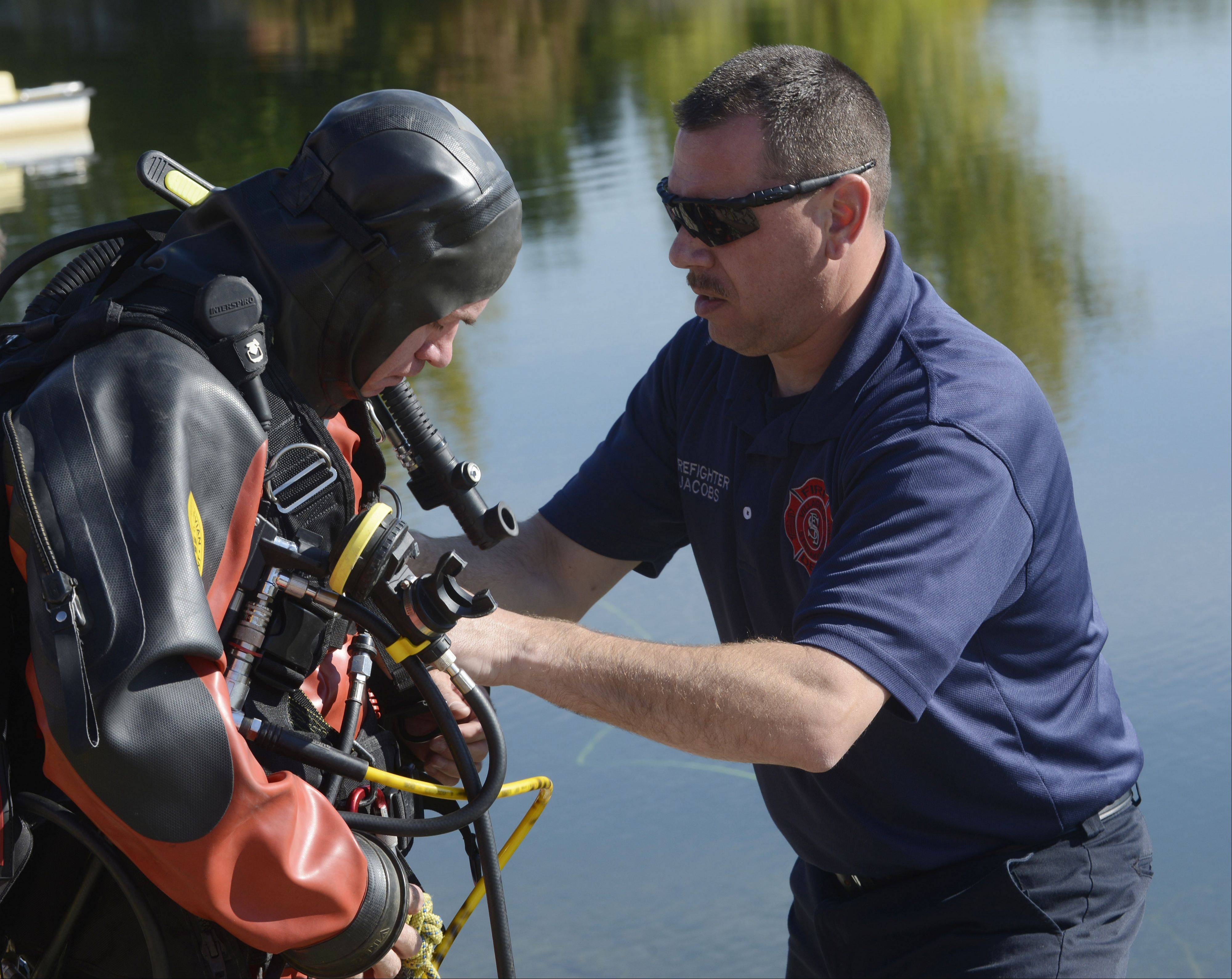 Elk Grove Village firefighter/paramedic Andy Laird receives assistance with his equipment from Streamwood firefighter/paramedic Gary Jacobs as the regional water rescue team from the Mutual Aid Box Alarm System (MABAS) demonstrates water rescue techniques for the division�s command officers Friday at Twin Lakes Recreation Area in Palatine.
