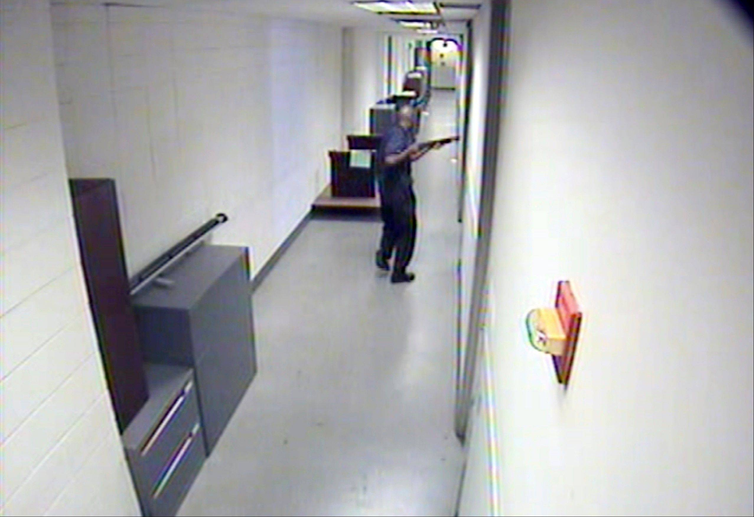 This image from video provided by the FBI, shows Aaron Alexis moves through the hallways of Building #197 at the Washington Navy Yard on Monday, Sept. 16, 2013, in Washington, carrying a Remington 870 shotgun. Alexis, a 34-year-old former Navy reservist and IT contractor, shot and killed 12 people inside a Navy Yard building last week before being killed in a shootout with police. (AP Photo/FBI)