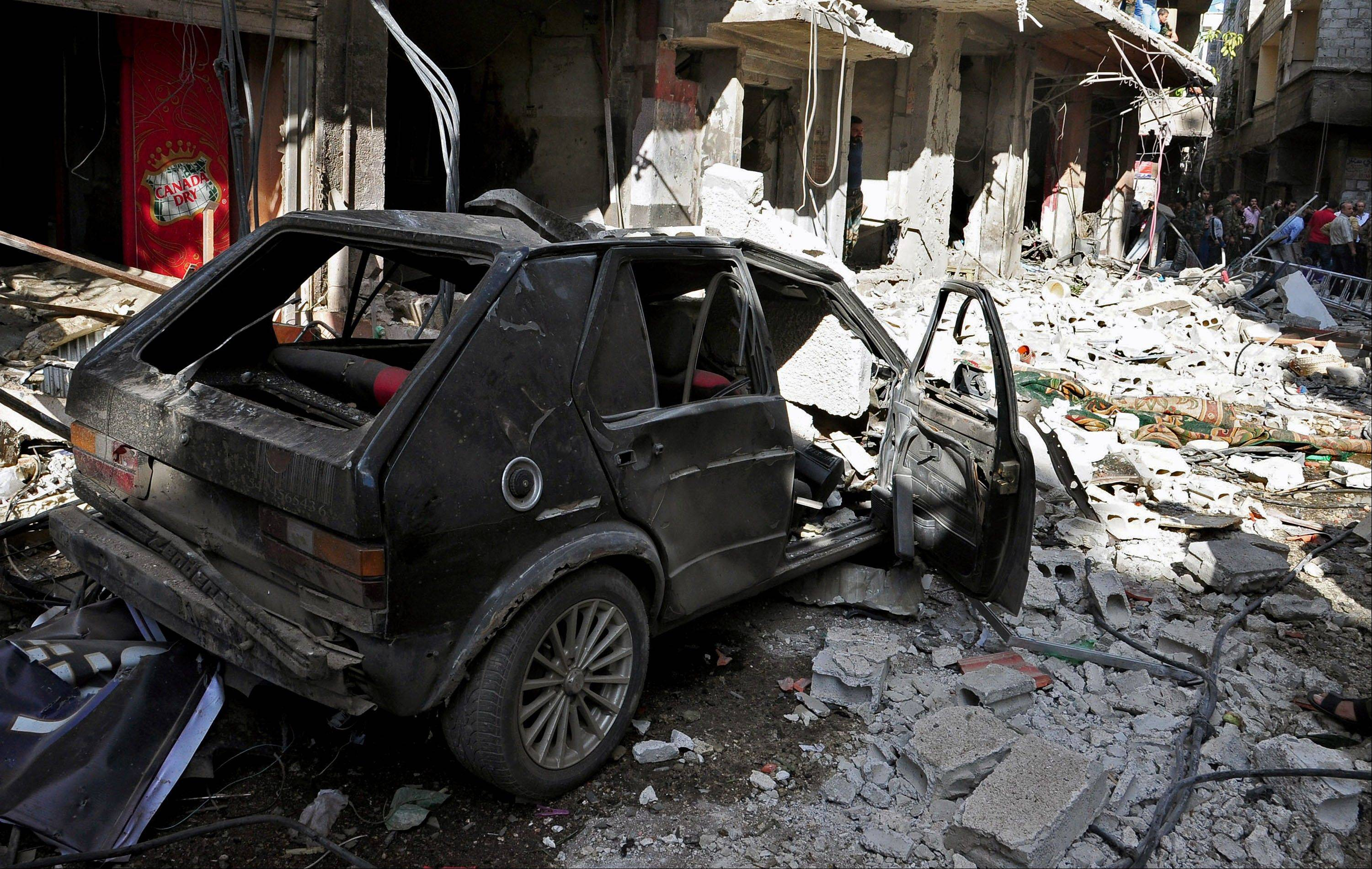 Syrian citizens gather at the scene of a car bomb explosion in the residential al-Tadhamon neighborhood in Damascus, Syria, Tuesday, Sept. 24, 2013.