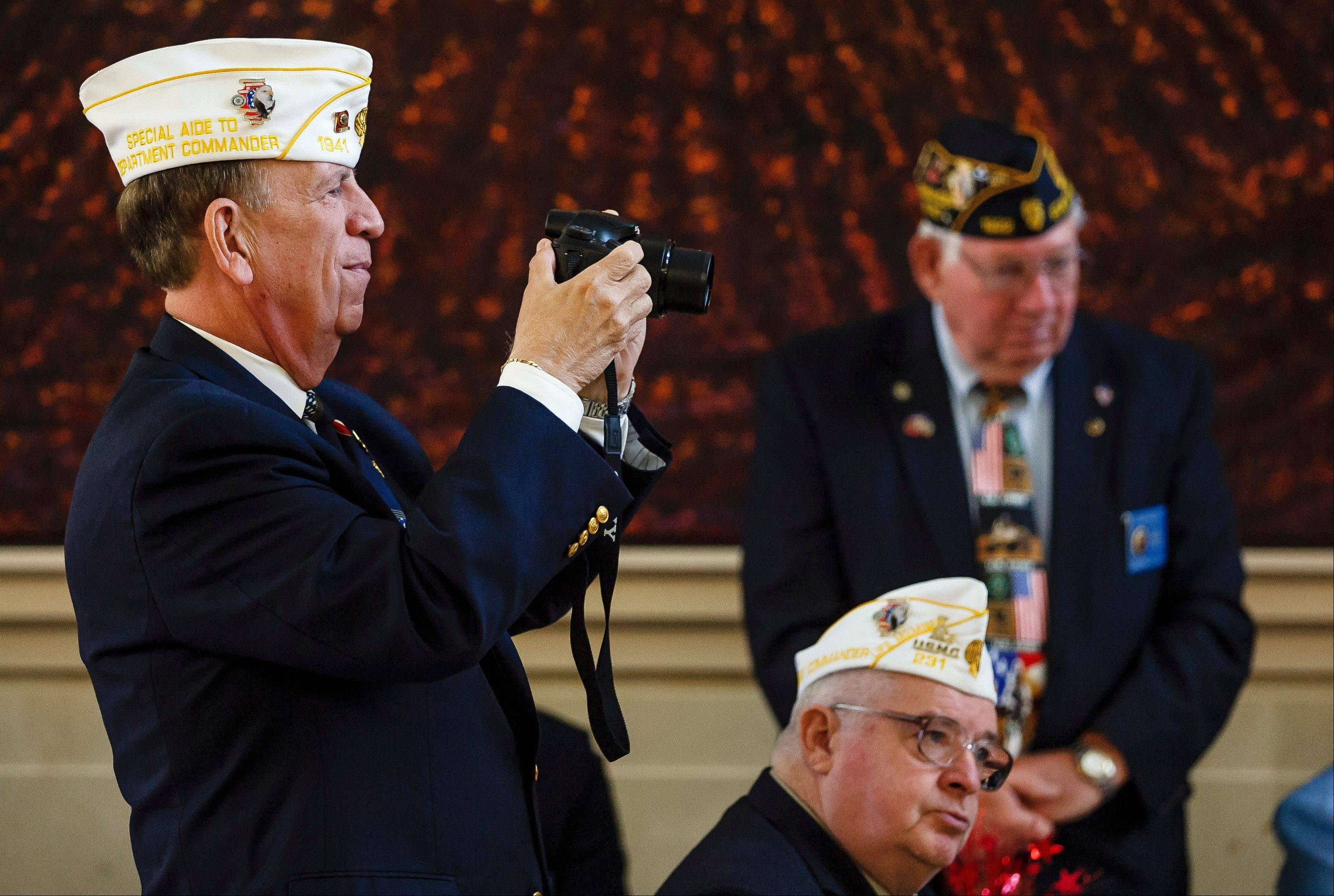 Western Springs resident Barry Cicero, left, an Army veteran who served as a nuclear weapons storage specialist in Alaska during the Vietnam era, snaps a photo of the Titan Fever Show Choir performing a medley of military anthems Tuesday during a ceremony celebrating the Illinois Veterans History Project in Springfield.