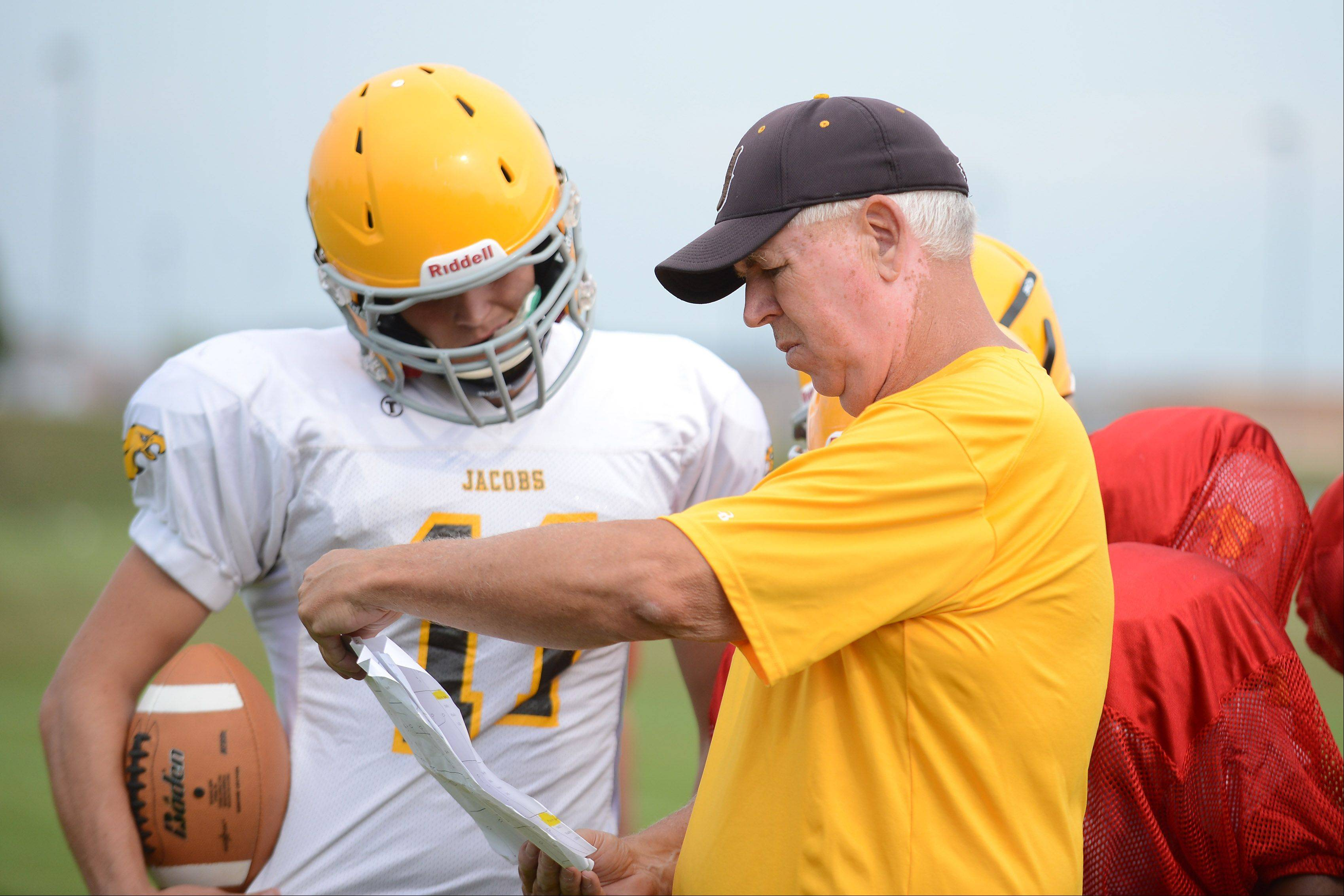 Jacobs senior quarterback Bret Mooney and Golden Eagles coach Bill Mitz go over a play during a preseason practice. Mooney enters Friday�s game against Woodstock just shy of 3,000 yards passing in his high school career.