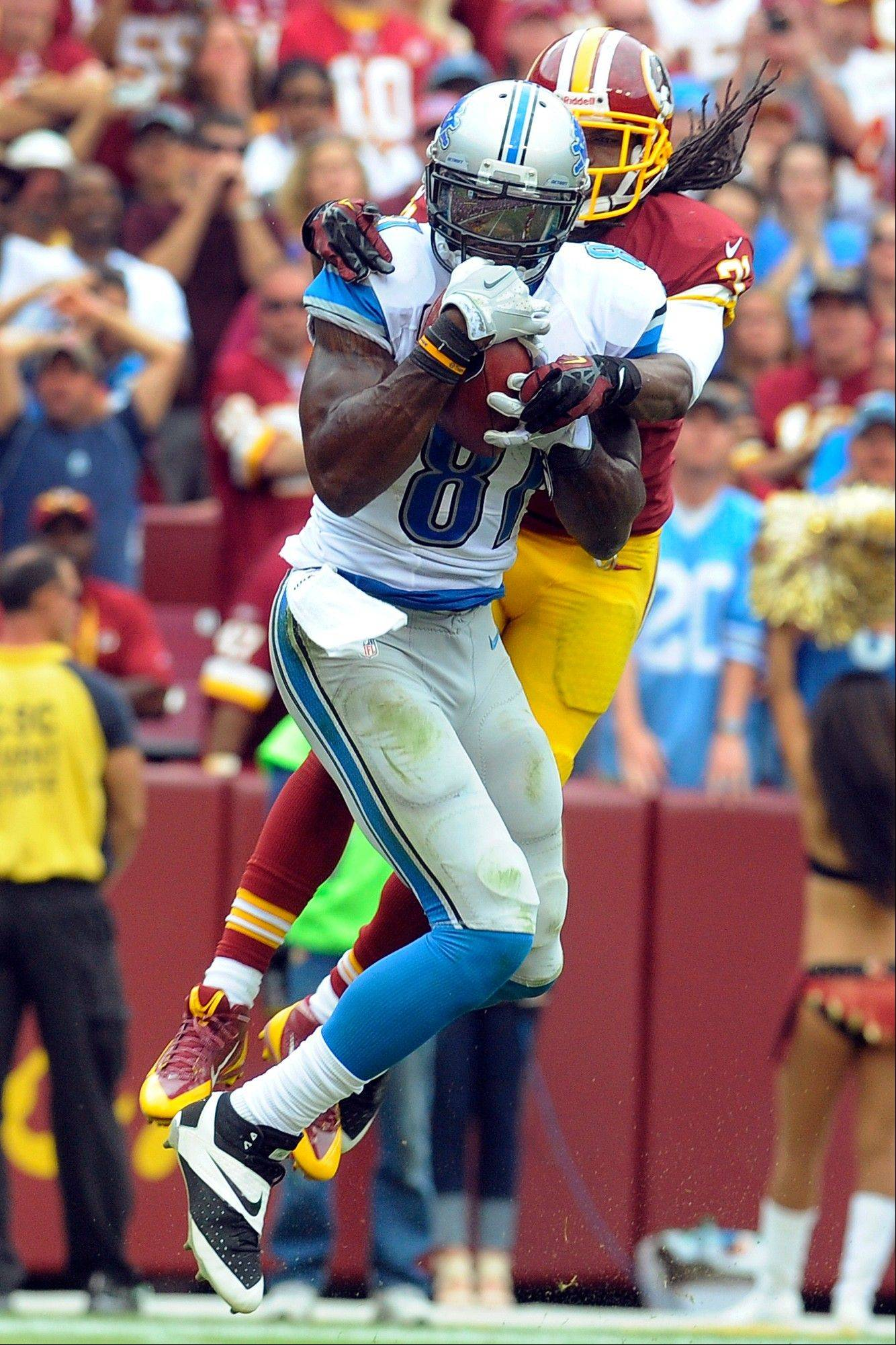 Detroit Lions wide receiver Calvin Johnson pulls in a touchdown pass under pressure from Washington Redskins strong safety Brandon Meriweather during the second half of a Sept. 22 game in Landover, Md.