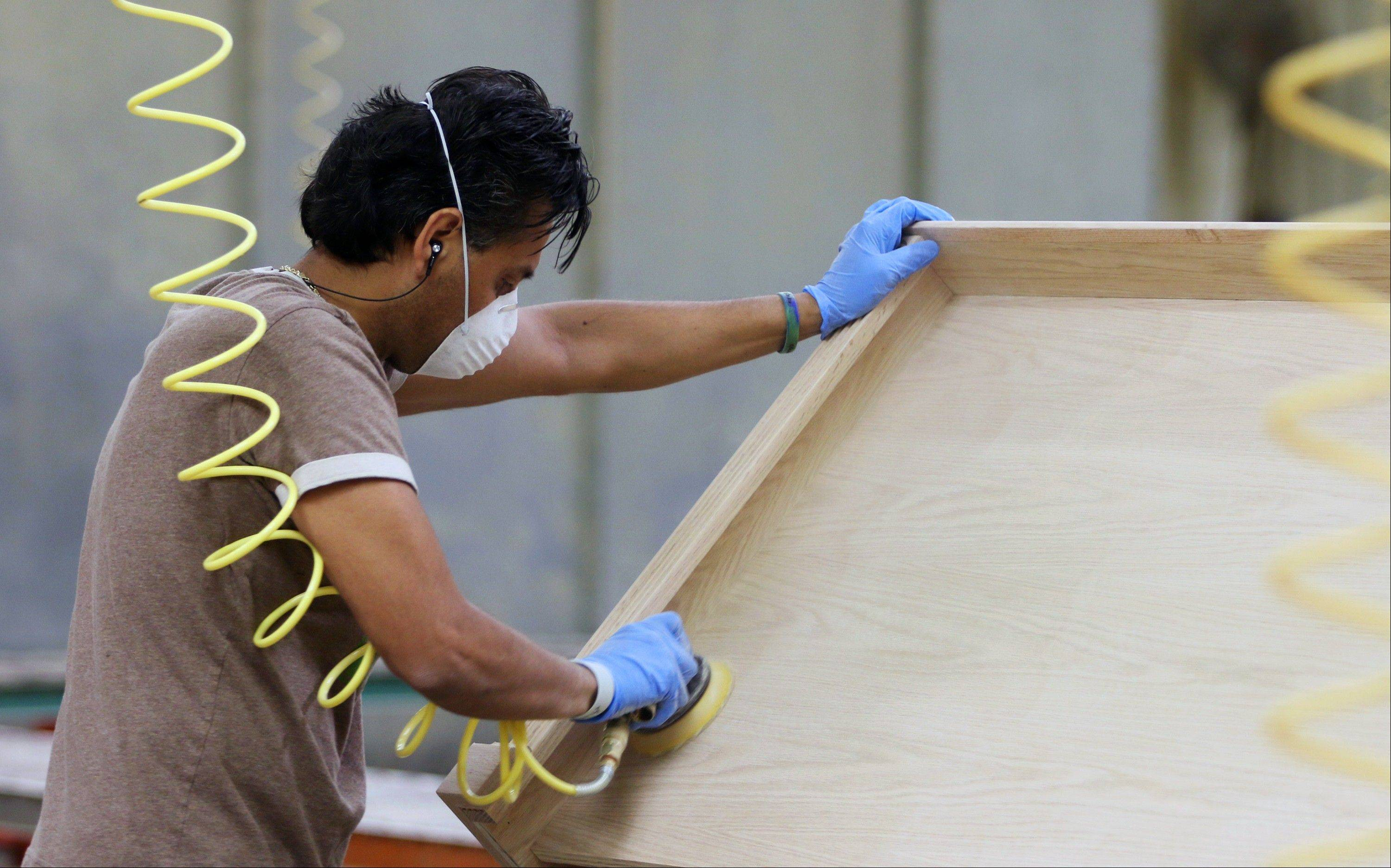 A worker sands a custom piece of furniture at the at Baker Road Furniture manufacturing facility in South Elgin. Companies placed slightly more orders in August for U.S. long-lasting manufactured goods, stepping up demand for cars, trucks and machinery. Even with the gain, business spending on factory goods may not be strong enough to accelerate economic growth in the July-September quarter.