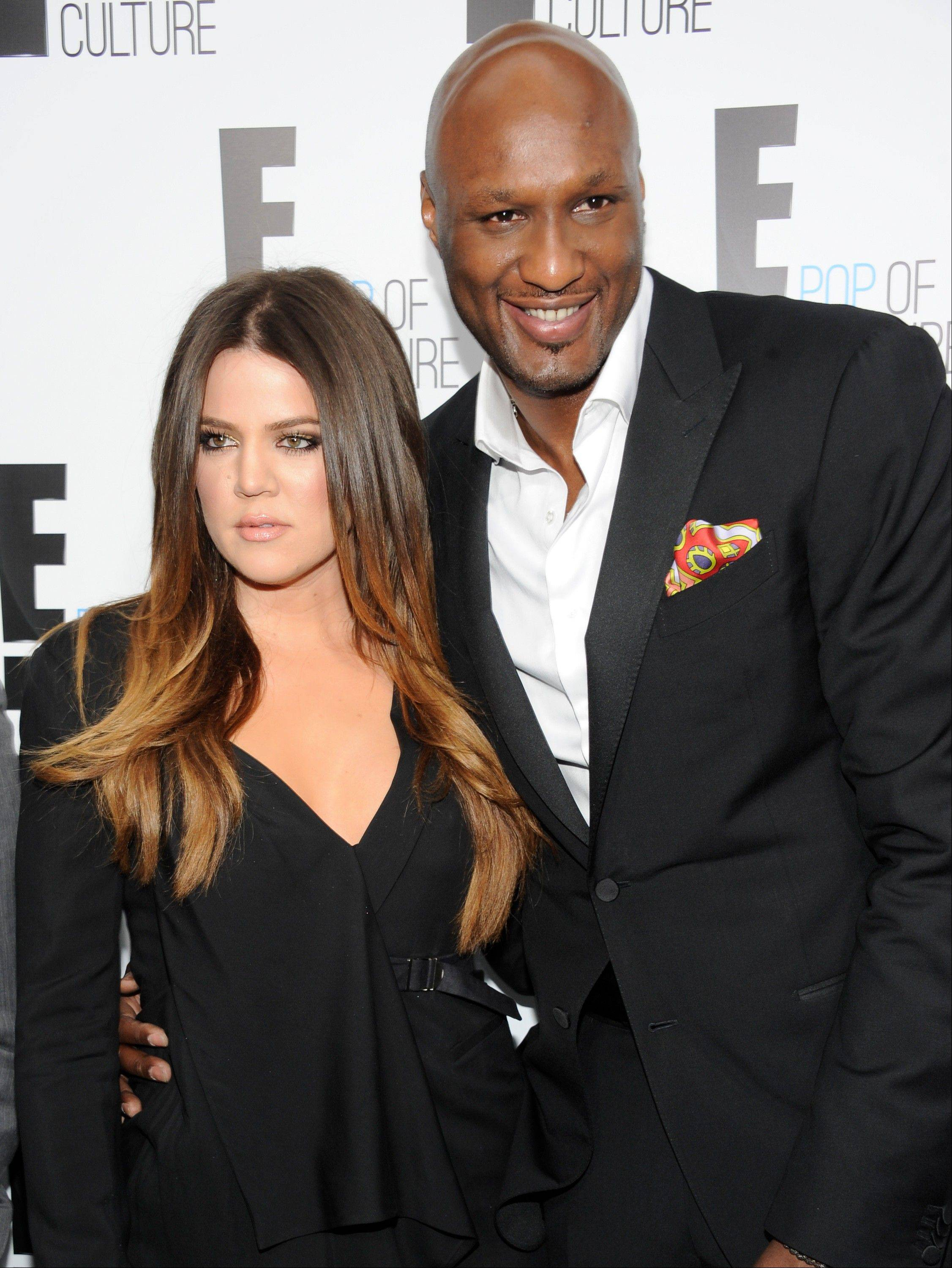 "Khloe Kardashian Odom and Lamar Odom pose at an E! Network event in New York. Odom is breaking his silence with his first post on Twitter since the NBA star was arrested and charged with driving under the influence last month. Odom tweeted ""Seeing the snakes"" on Tuesday night, Sept. 24, 2013, in his first post since his Aug. 30 arrest."