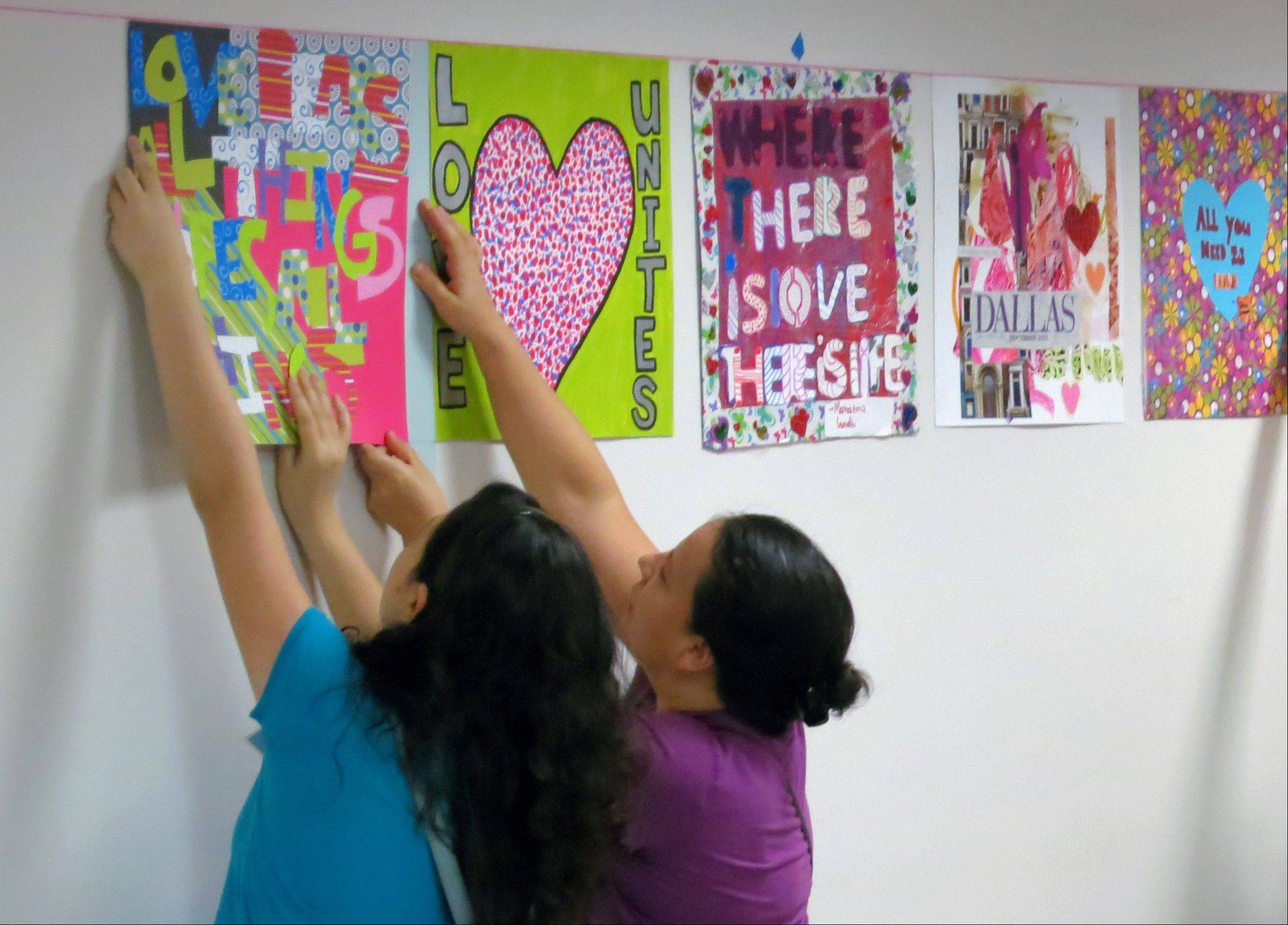 Brenda Castaneda, left, and Irma Castaneda help the nonprofit art organization 29 Pieces hang art in the hallways at Parkland Memorial Hospital in Dallas.