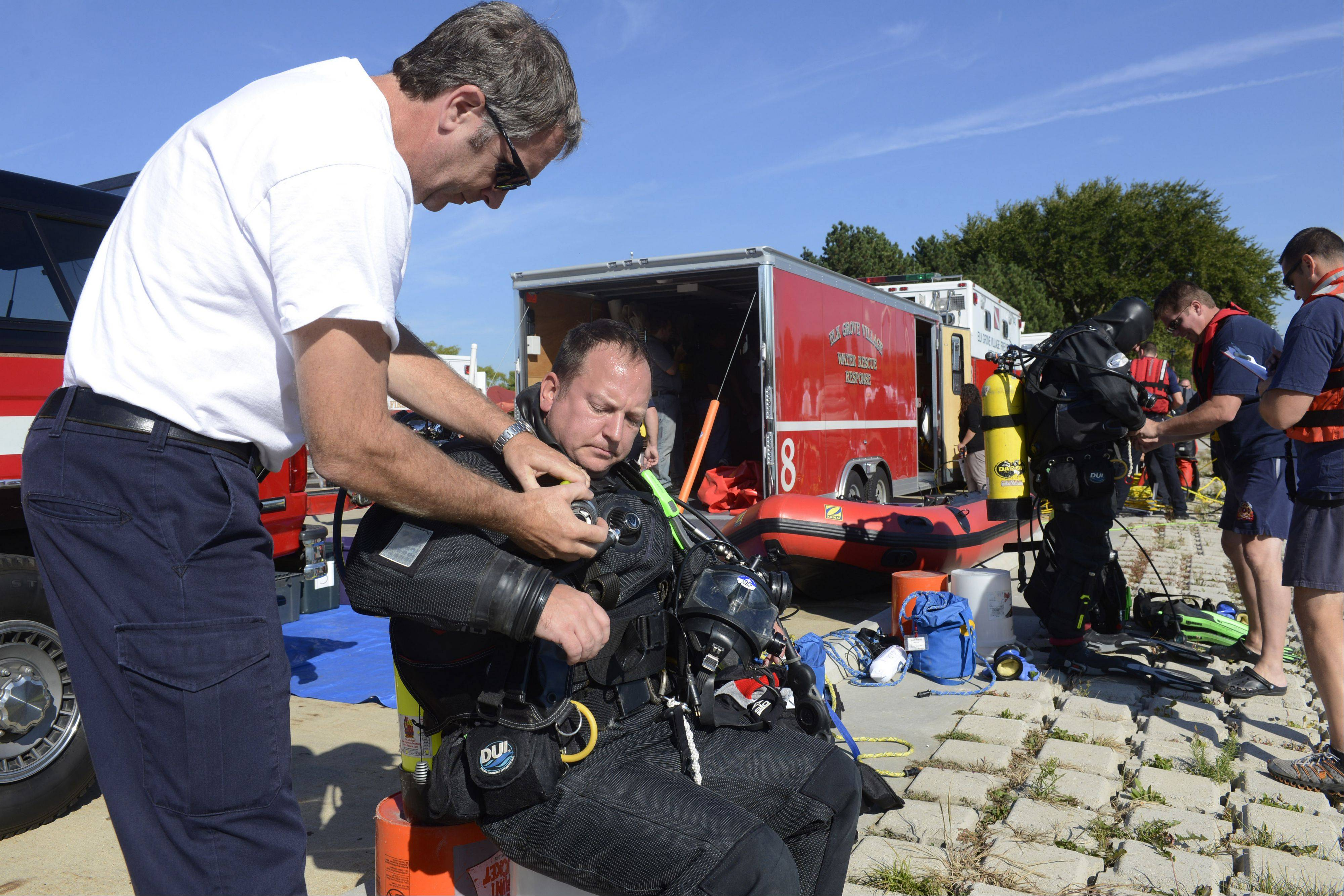 Hoffman Estates Fire Captain Mike Hartman helps firefighter/paramedic Scott Mullis with his equipment as the regional water rescue team from the Mutual Aid Box Alarm System (MABAS) demonstrates water rescue techniques for the division's command officers Friday at Twin Lakes Recreation Area in Palatine.
