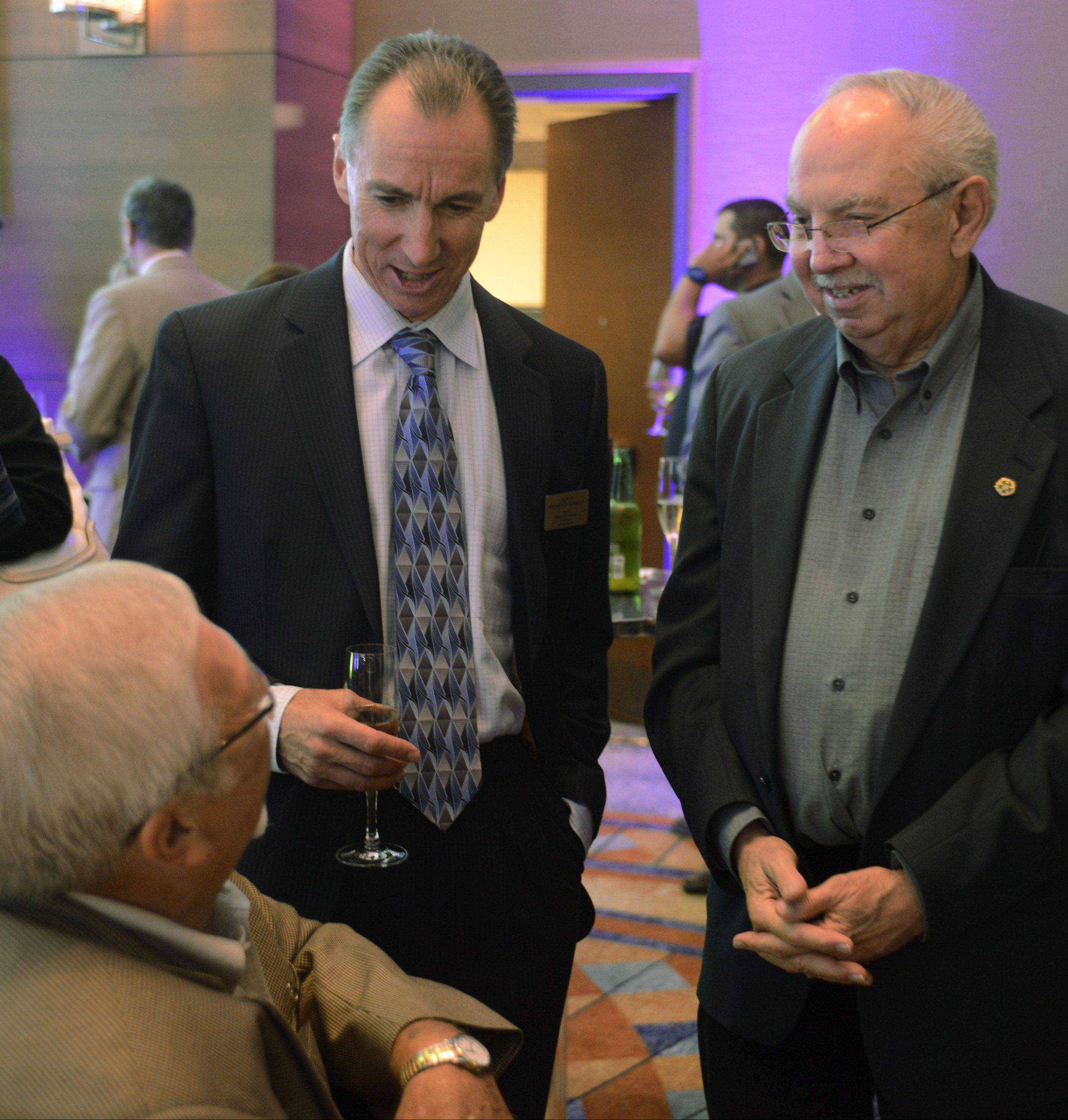 Charles Witherington-Perkins, Arlington Heights' director of planning and community development, standing left, and Schaumburg Mayor Al Larson, right, chat with Schaumburg Trustee Frank Kozak Wednesday at an unveiling of the new Meet Chicago Northwest name and logo.