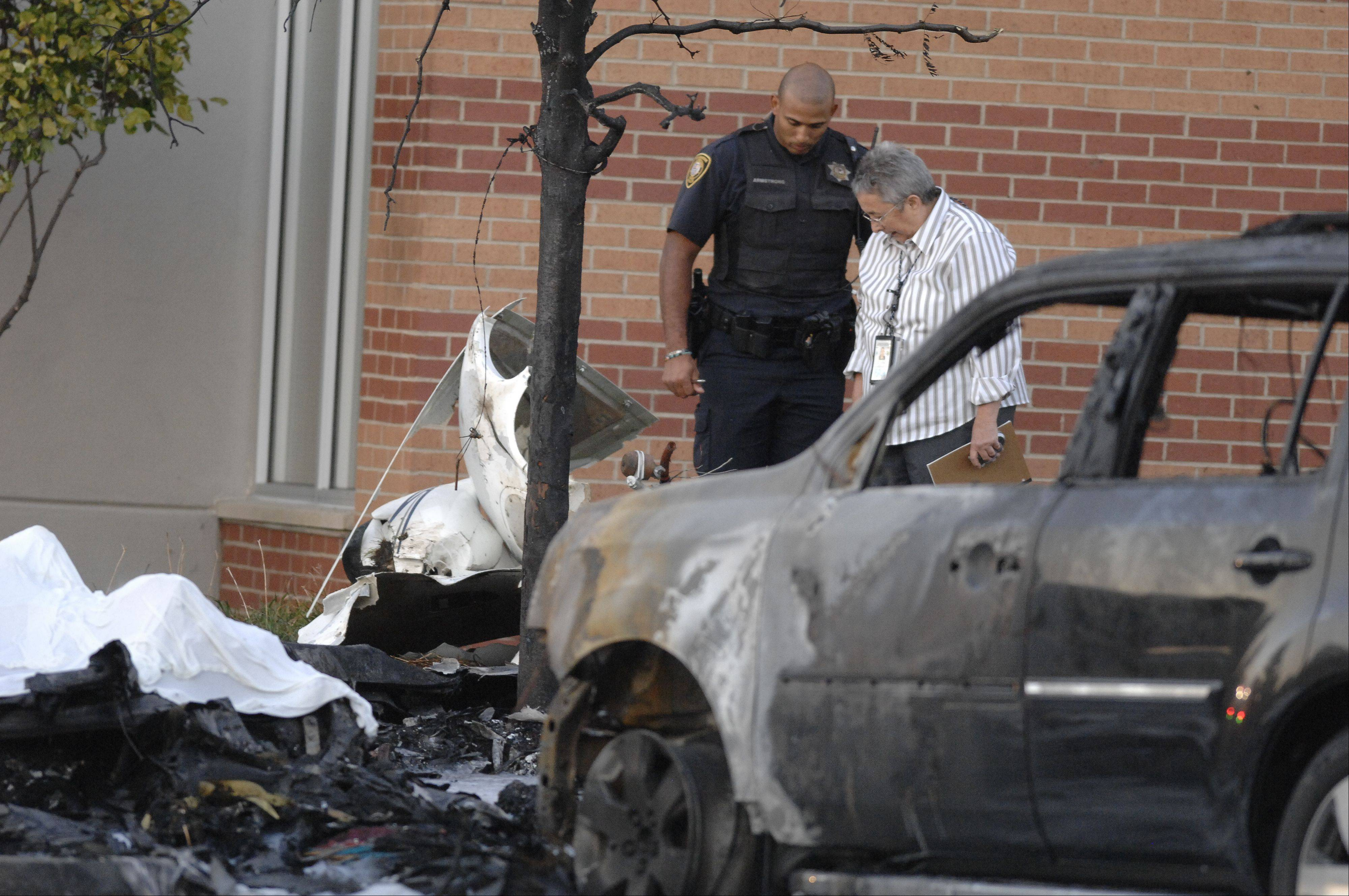 Investigators examine the crash site of a plane crash Wednesday in the parking lot of a Chase bank in Bolingbrook. Police say one person died and one is hospitalized from the crash.