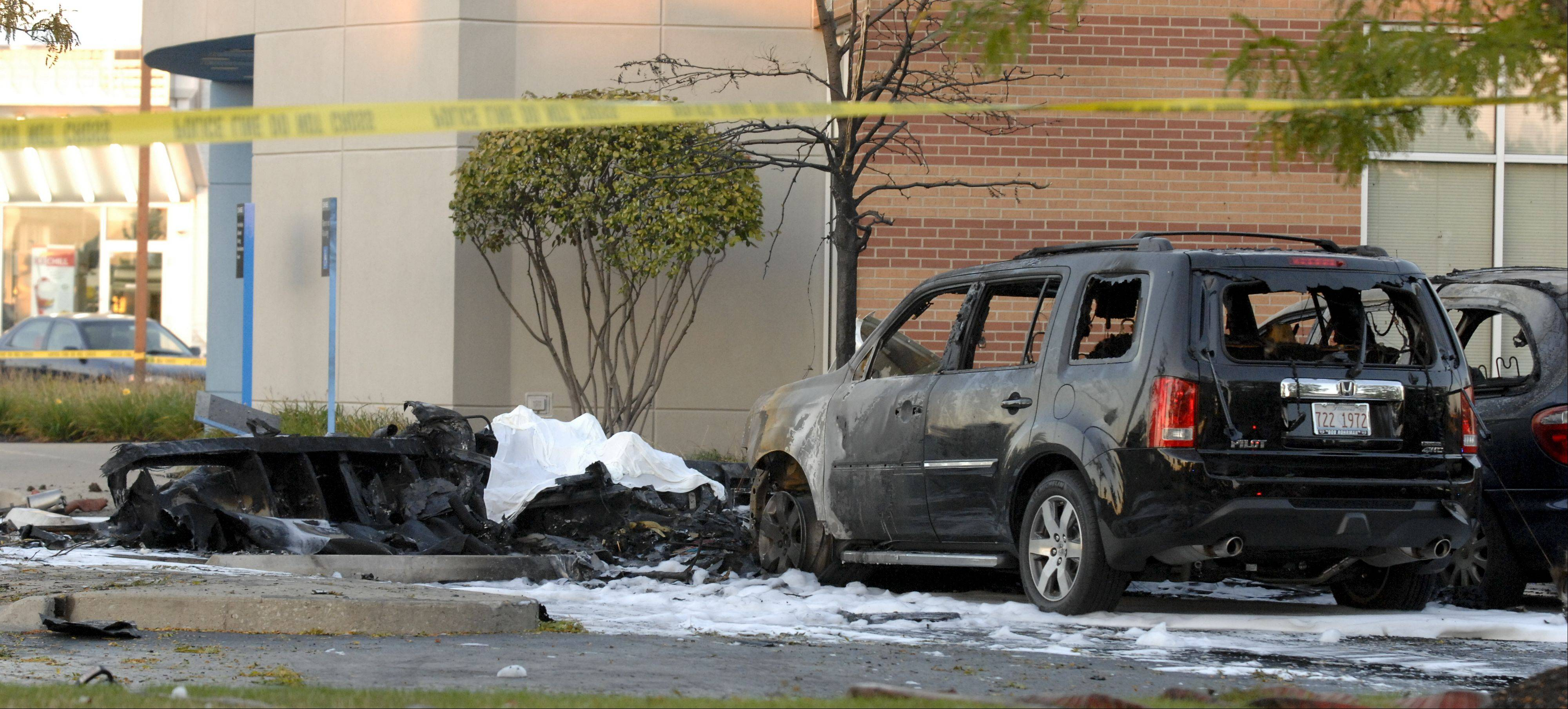 Investigators examine the site of a plane crash Wednesday in the parking lot of a Chase bank on Weber Road near the Clow International Airport in Bolingbrook.