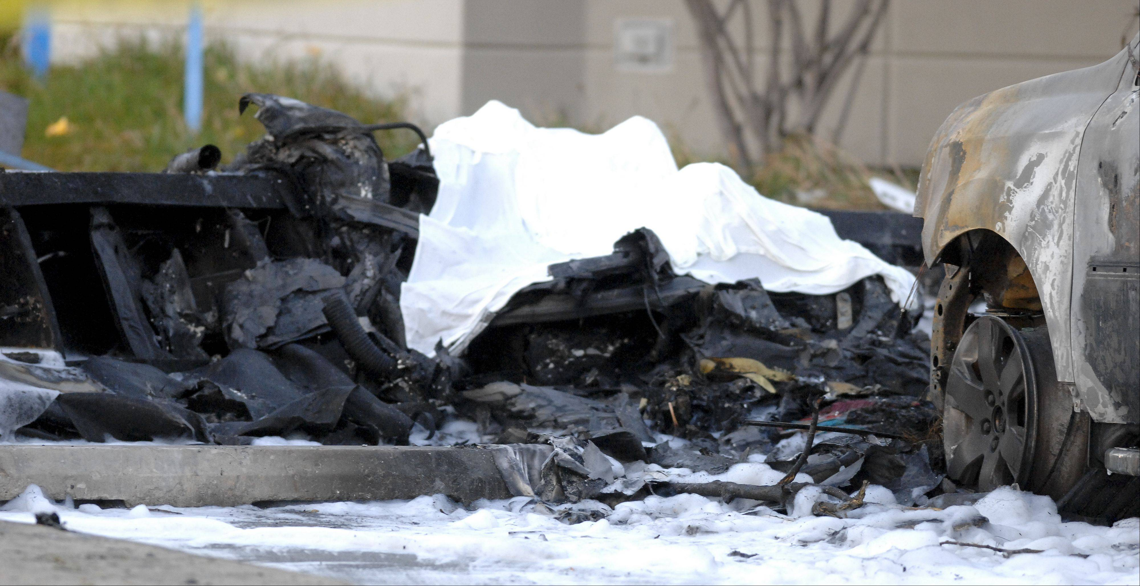 A white sheet covers part of what remains of a small plane that crashed Wednesday in the parking lot of a Chase bank on Weber Road near the Clow International Airport in Bolingbrook.