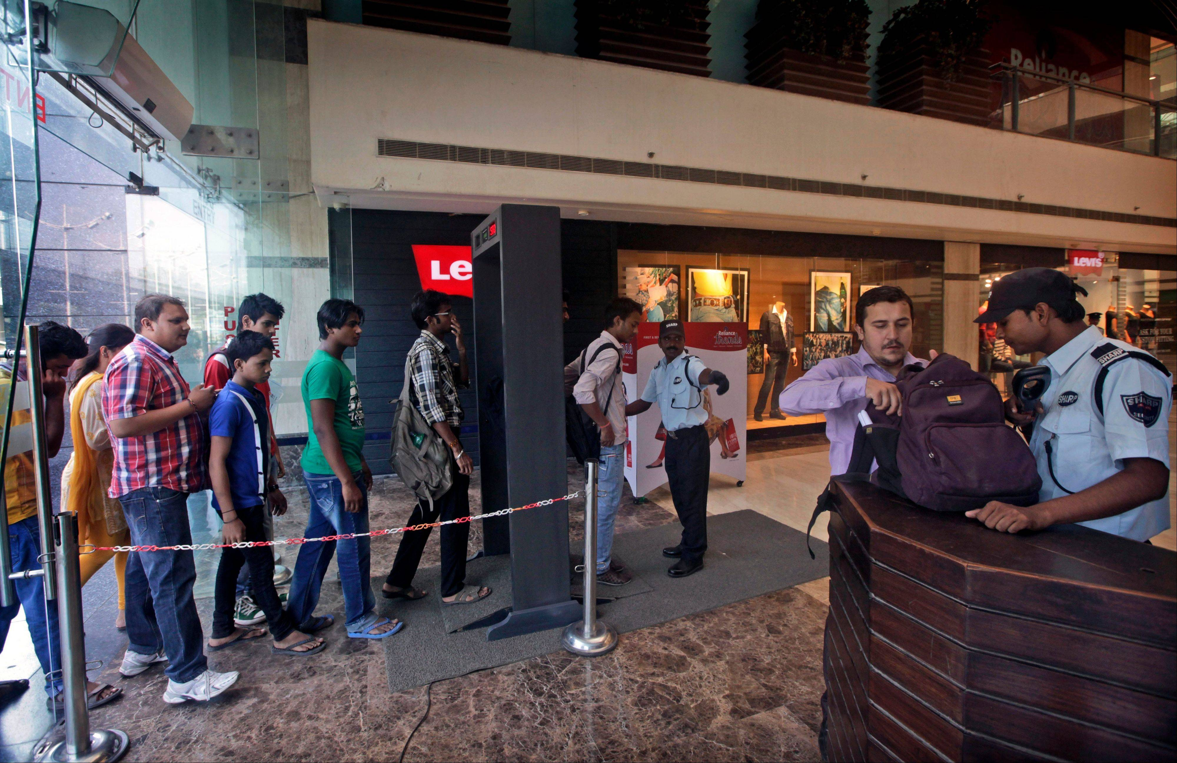 Shoppers walk through a metal detector before they are frisked by a private security guard as another security guard, right, checks a bag at the entrance to a shopping mall in New Delhi, India. Shopping centers across the globe are adding guards and increasing security following the attack in Nairobi over the weekend.