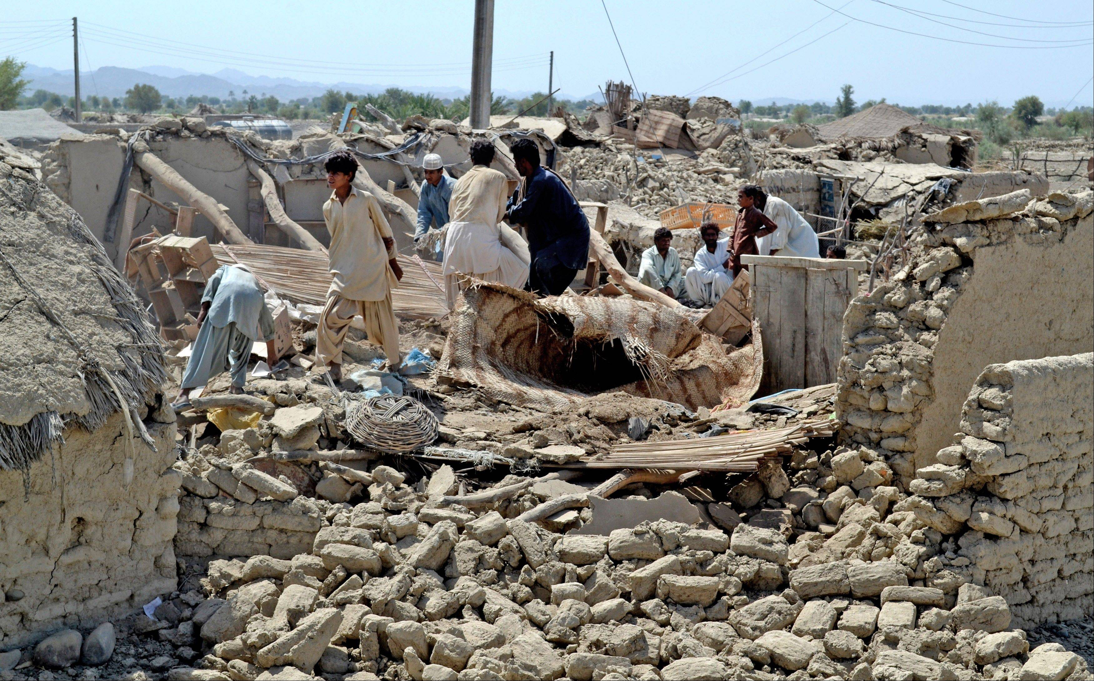 Pakistani villagers look for belongings amid the rubble of their destroyed homes following an earthquake in the remote district of Awaran, Baluchistan province, Pakistan, Wednesday, Sept. 25, 2013.