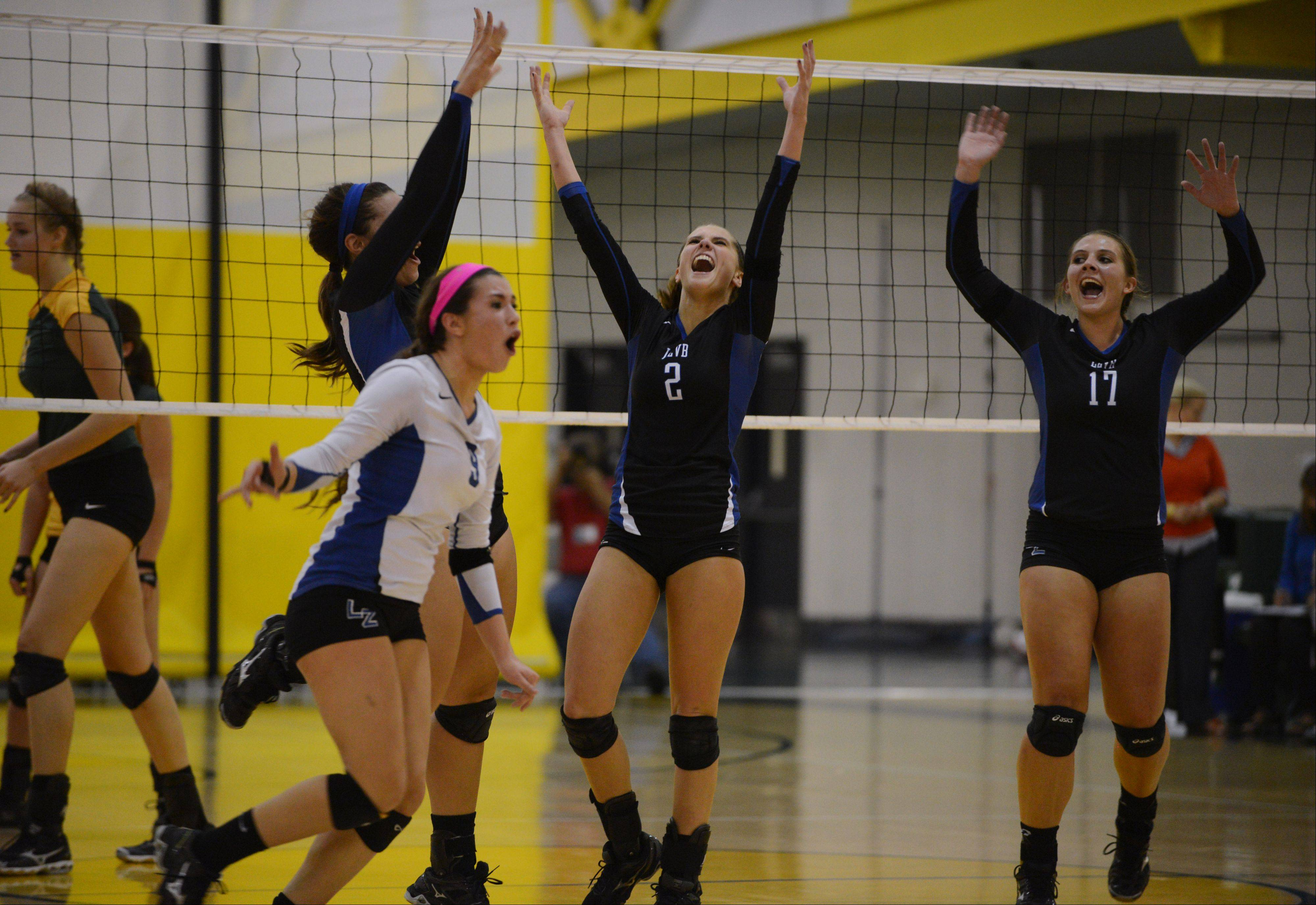 Lake Zurich players Ashley Dina (9), Mickenzie Andrews (2) and Allie McIlwain (17) celebrate their set two win over Stevenson on Wednesday in Lincolnshire.