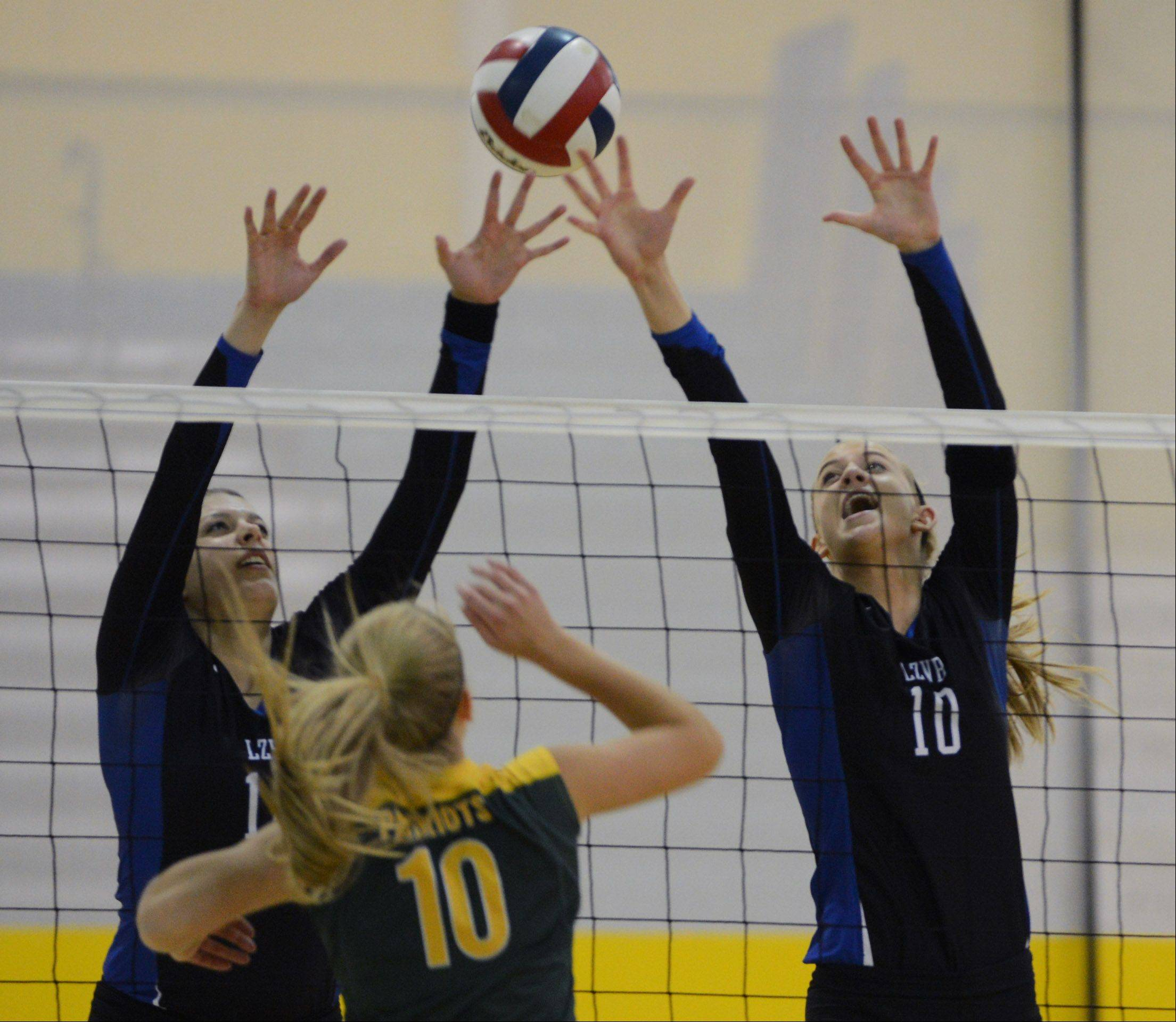 Lake Zurich's Sydney Glover, left, and Kristen Walding try to block a shot by Stevenson's Jennifer Kapov (10) during Wednesday's volleyball game in Lincolnshire.