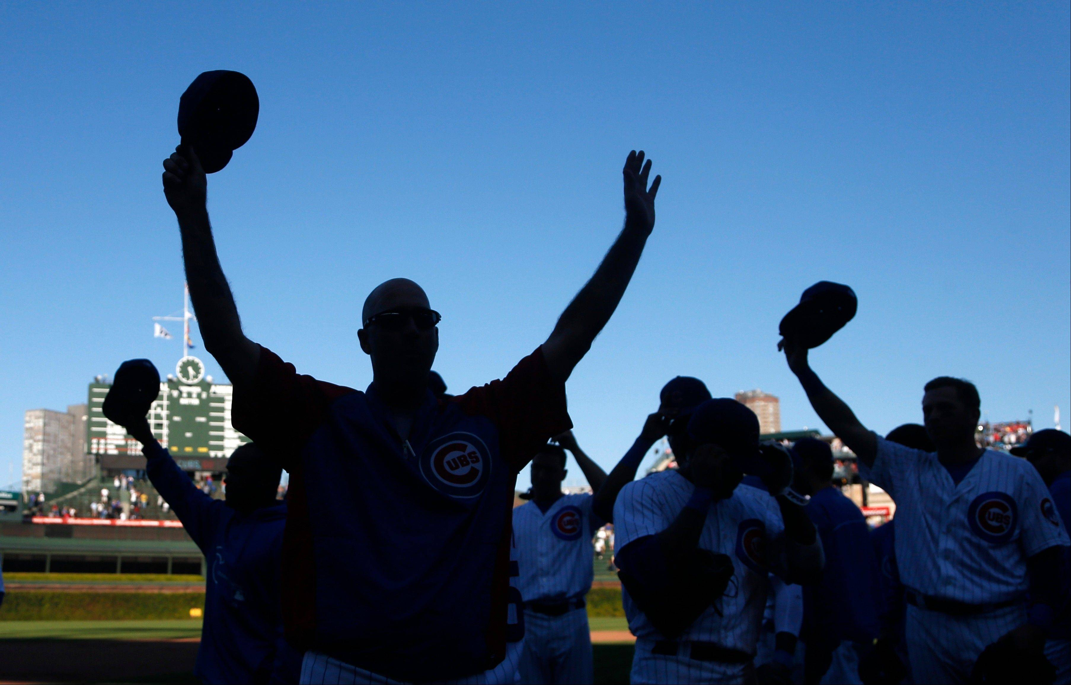 Cubs manager Dale Sveum, left, and the team salute the fans as the Cubs celebrate their 4-2 win over the Pittsburgh Pirates after their last home baseball game of the season Wednesday in Chicago.