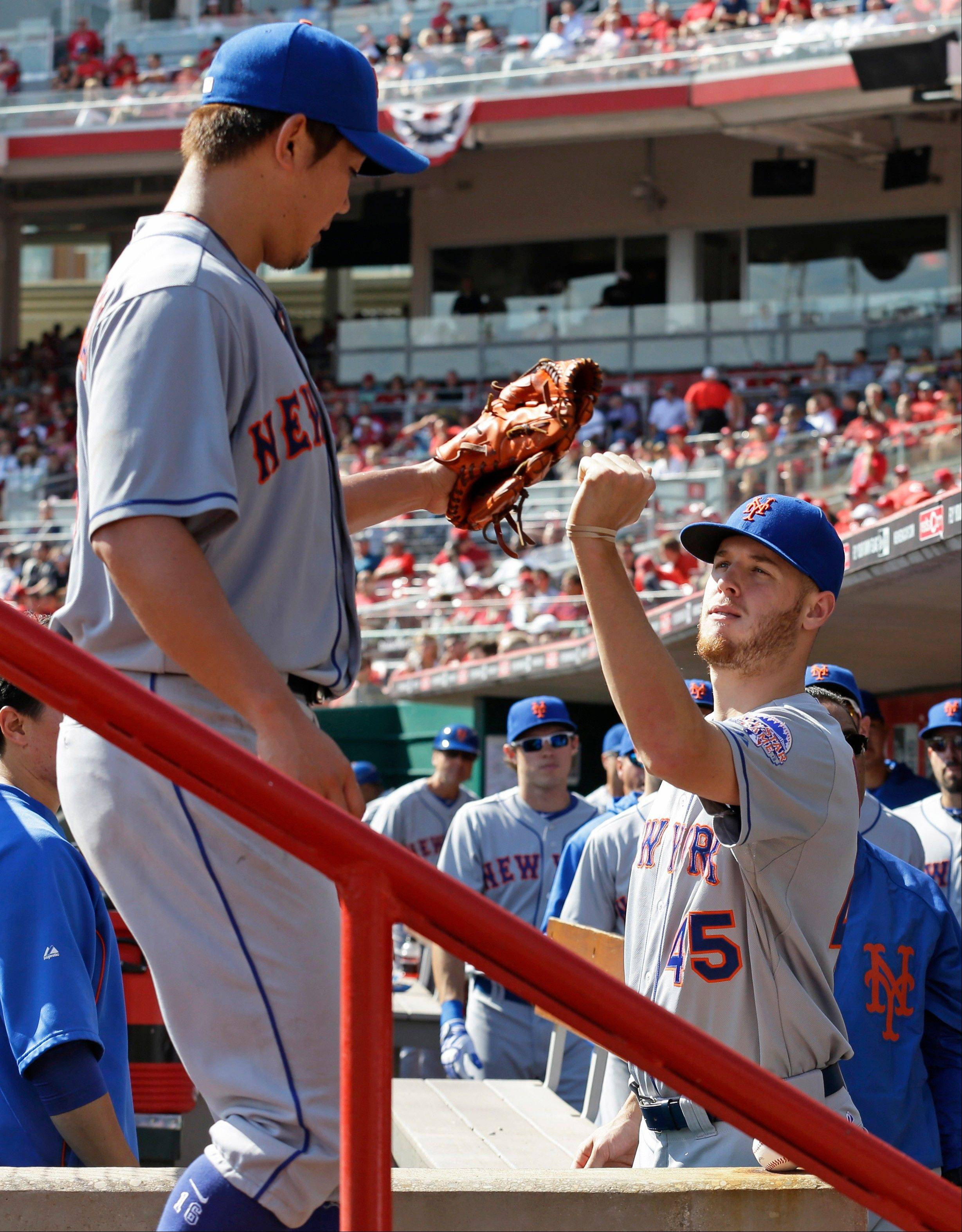 New York Mets starting pitcher Daisuke Matsuzaka is congratulated by Zack Wheeler (45) after Matsuzaka was taken out in the eighth inning of a baseball game against the Cincinnati Reds, Wednesday in Cincinnati. Matsuzaka was the winning pitcher in the game won by New York 1-0.