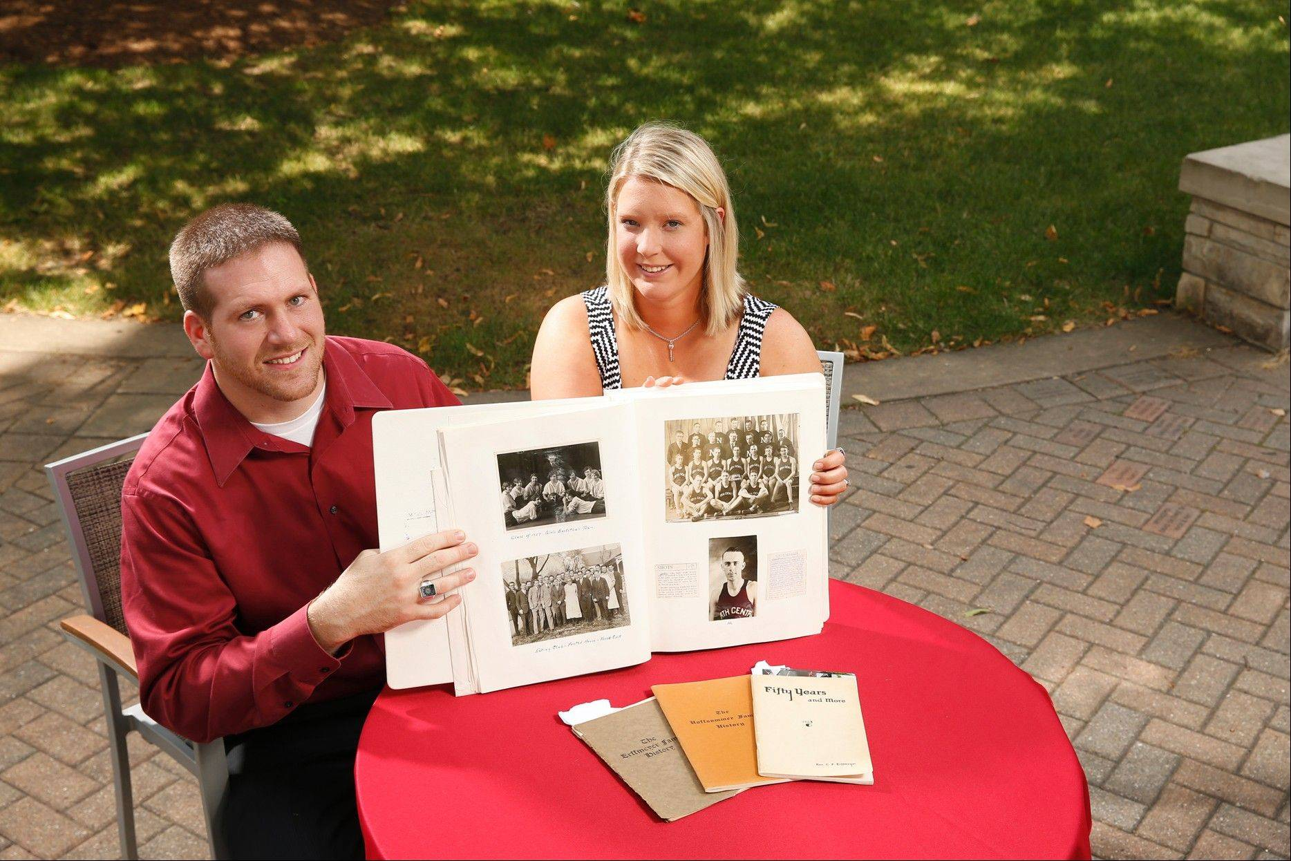 "Caitlin ""Cait"" Neuman Schlorff and her husband, Tony, show the family scrapbook that revealed Cait's family's deep ties to North Central College. The couple each earned degrees in 2011, 136 years after her first ancestor enrolled in classes at the school."
