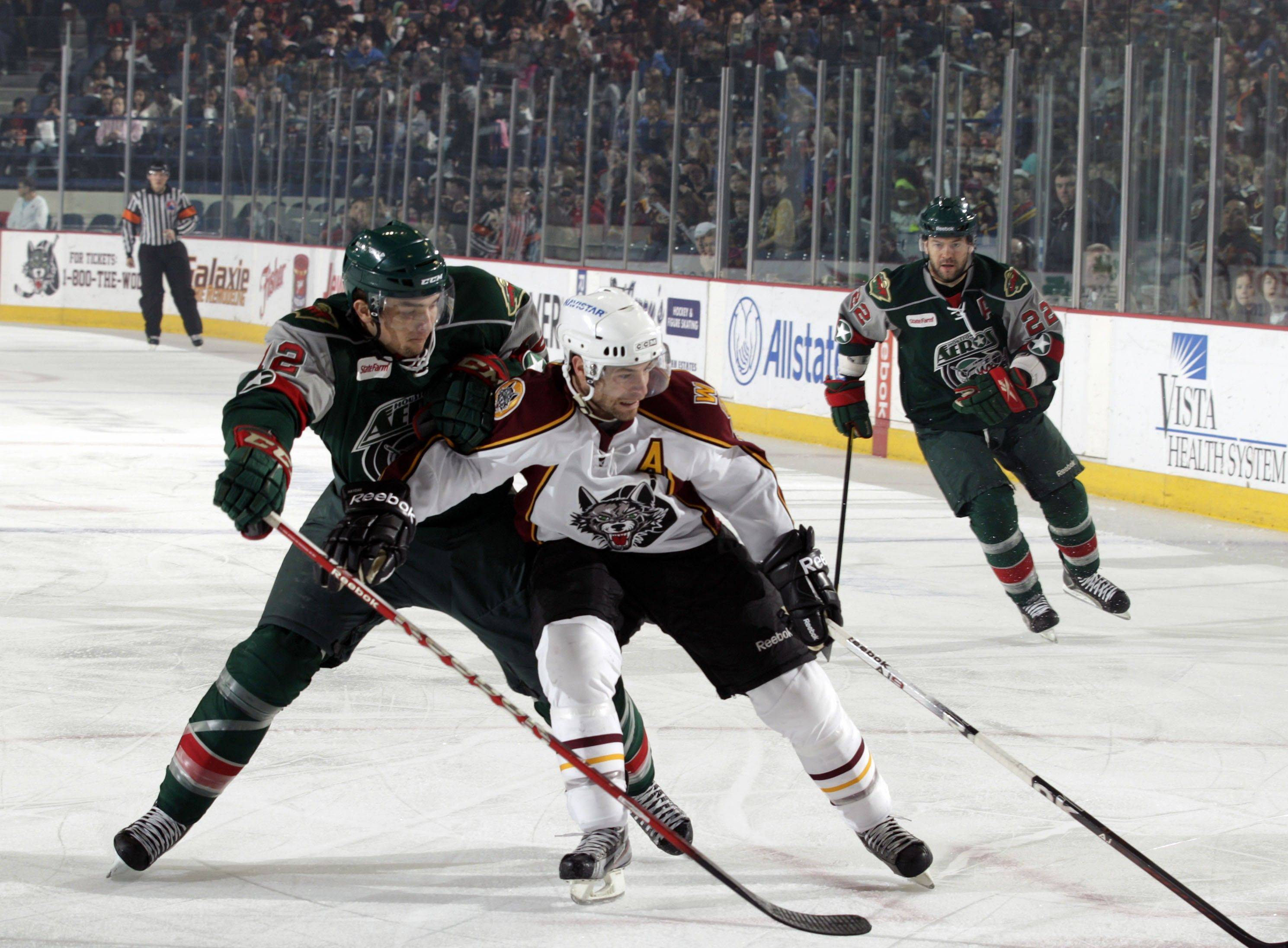 Chicago Wolves winger Darren Haydar battles to maintain control of the puck against Cody Almond of the Houston Aeros at Allstate Arena.
