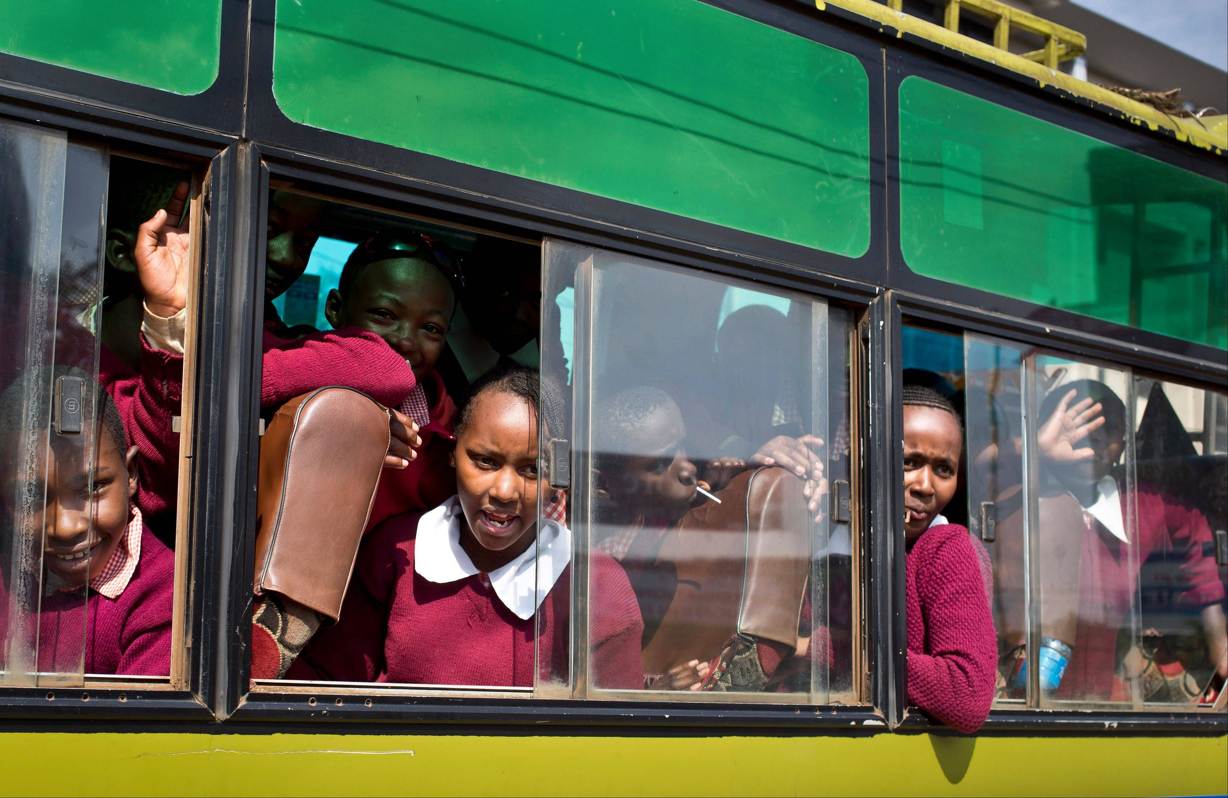 Kenyan girls in a school bus look across at the scene as they drive past a road leading to the Westgate Mall in Nairobi on Thursday.