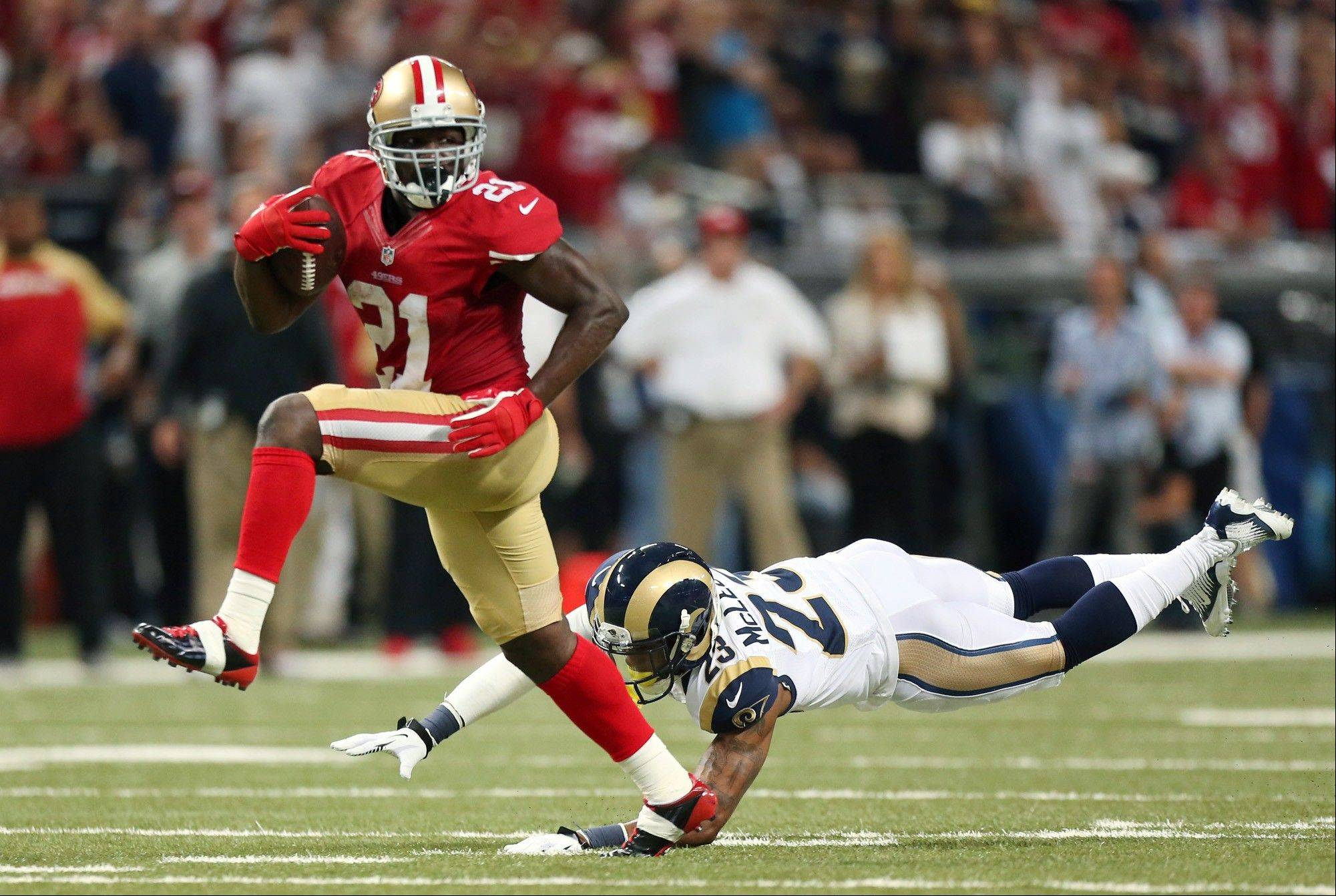 San Francisco 49ers running back Frank Gore eludes a tackle Rams safety Rodney McLeod en route to a 34-yard touchdown Thursday in St. Louis.